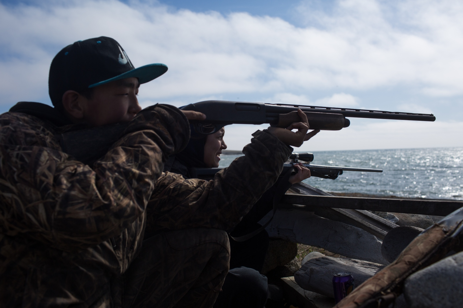 Chase Apassingok, 13, and his sister, Danielle Apassingok, 17, sit in a seal blind, watching the sea for seals.