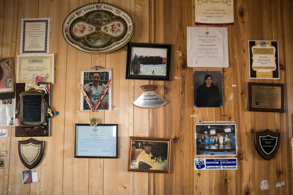 "A wall in Daniel Apassingok's father's home in Gambell, Alaska, which boasts photos and a ""young providers award"" of his grandson, Chris."