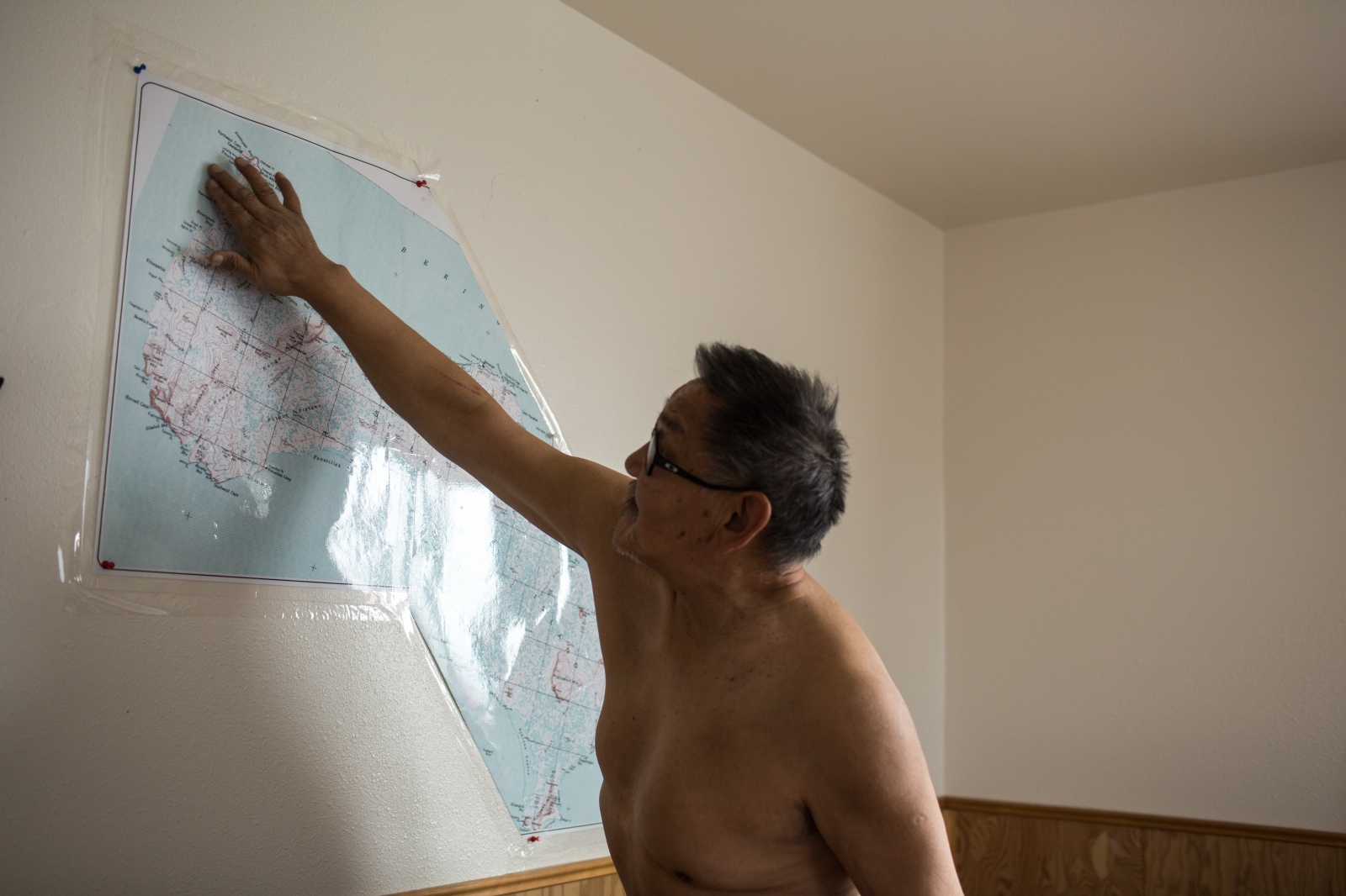 Mike Apatiki, Chris's grandfather, gestures on a map of St. Lawrence Island where the path the whales typically trake in the sea.