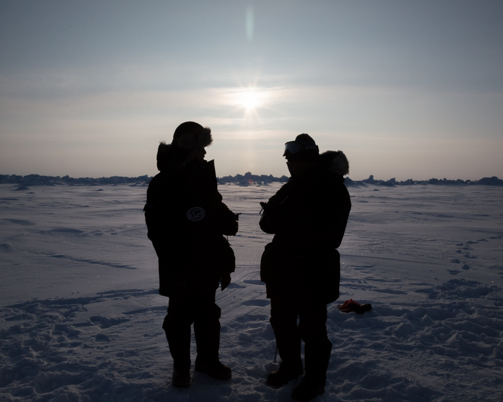 An expedition guide speaks with a client during an hour-long visit to the geographic North Pole, made by helicopter from the Russian Barneo Ice Camp. 2016.
