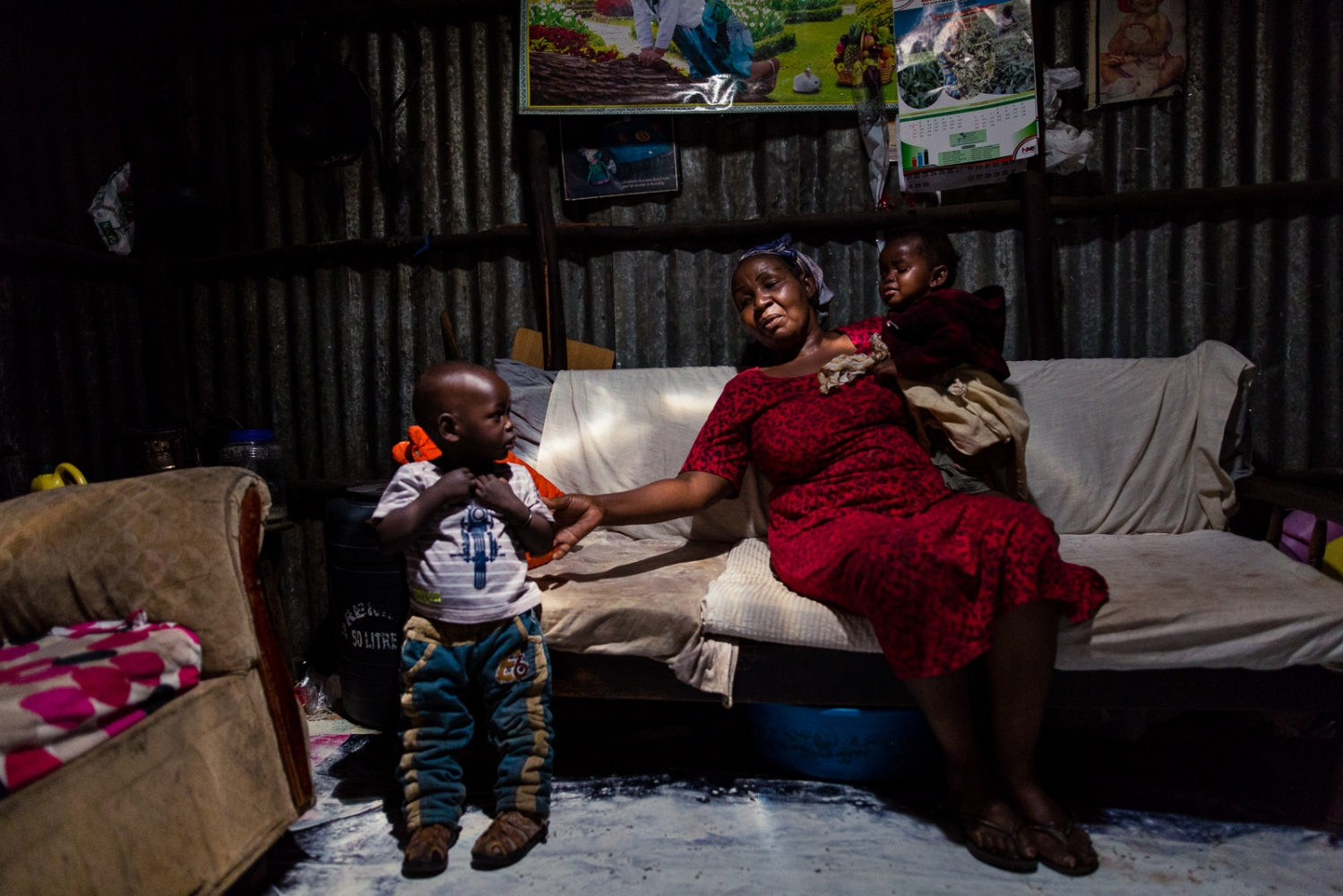 """Nairobi, KENYA, February 20, 2017: Elizabeth Kamau, 60, inside her hut in the Korogocho township with one of her ten grandchildren and the child of her adopted daughter. """"I like being a good role model to children by showing them that a woman can be strong and empowered"""", she says. Elizabeth has been training with the 'Shosho Jikinge' (Engl.: 'Grandmother defend yourself') group since five years and has succesfully applied self-defense techniques to fight off potential sexual attackers."""