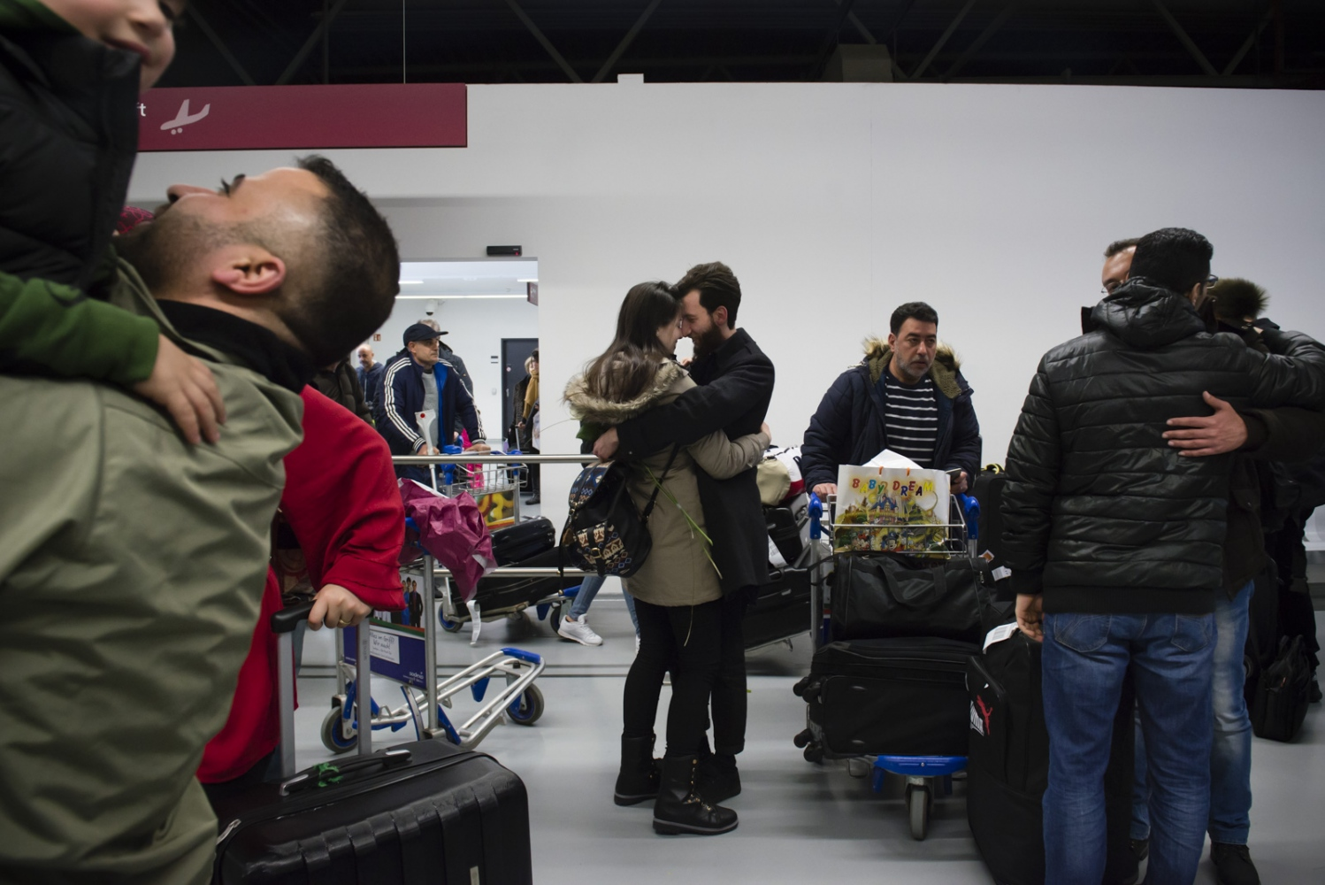 BERLIN  | GERMANY | 2017-03-09 | Reunited after 27 months, Ali (27) welcomes his wife, Marwa (23) at Schonefeld Airport. In the background Syrian families welcome their loved ones who just arrived in Berlin, Germany.