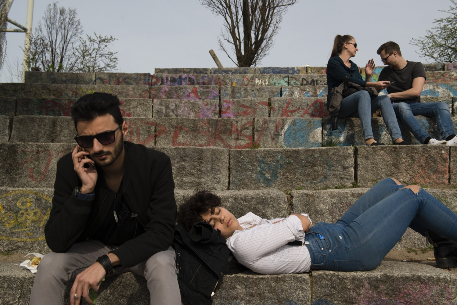 BERLIN | GERMANY | 2017-03-31 | Ramez (24) and Salwana (19) hang out at Mauer Park on a sunny saturday. The two Syrian friends met at language schools where both study German to enter university and have become close friends ever since. Ramez and Salwana have different reasons and have taken route out of Syria, but both chose Berlin as home and are well adapted to the german culture.