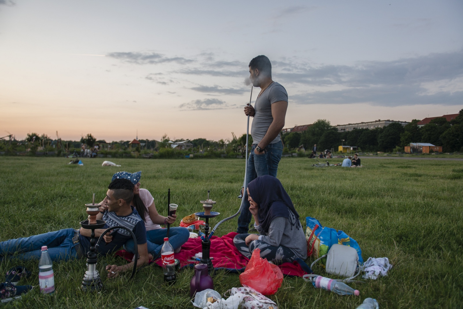 BERLIN | GERMANY | 2016-06-06 | Two Syrian couple spend their Sunday afternoon picnicking in Tempelhof, a vast great area that used to be the largest airport in europe during WWII. The space now hosts families and young people on warm days while one of the largest refugee camps in Berlin remains in the buildings of the airport.