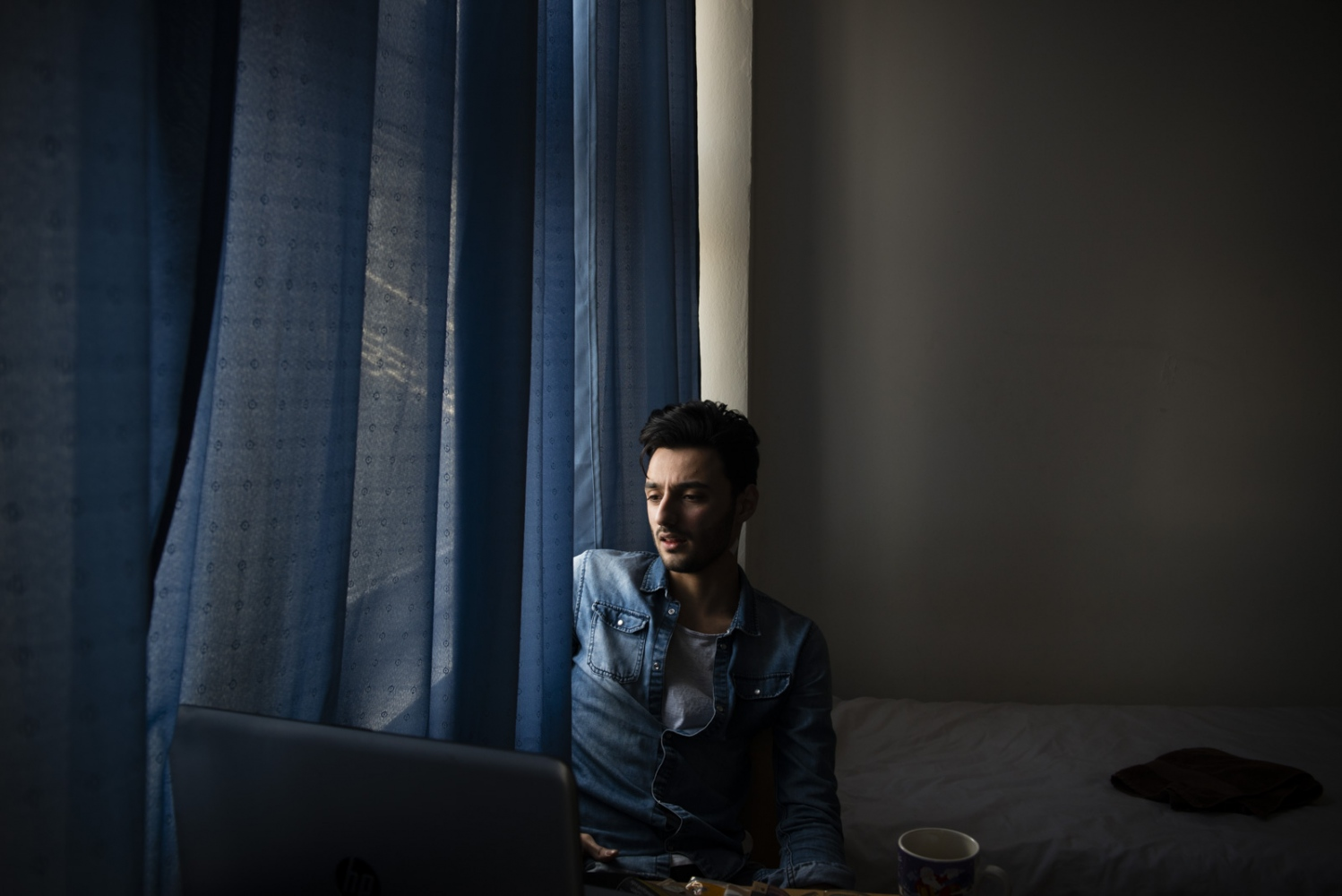 BERLIN| GERMANY | 2017-03-04 | Ramez (24), on his moving day, checks his Facebook in his old room. With the housing crisis that is going on in Berlin and across Germany, finding an apartment or a room to rent has become a nearly impossible task, for locals as well as refugees.