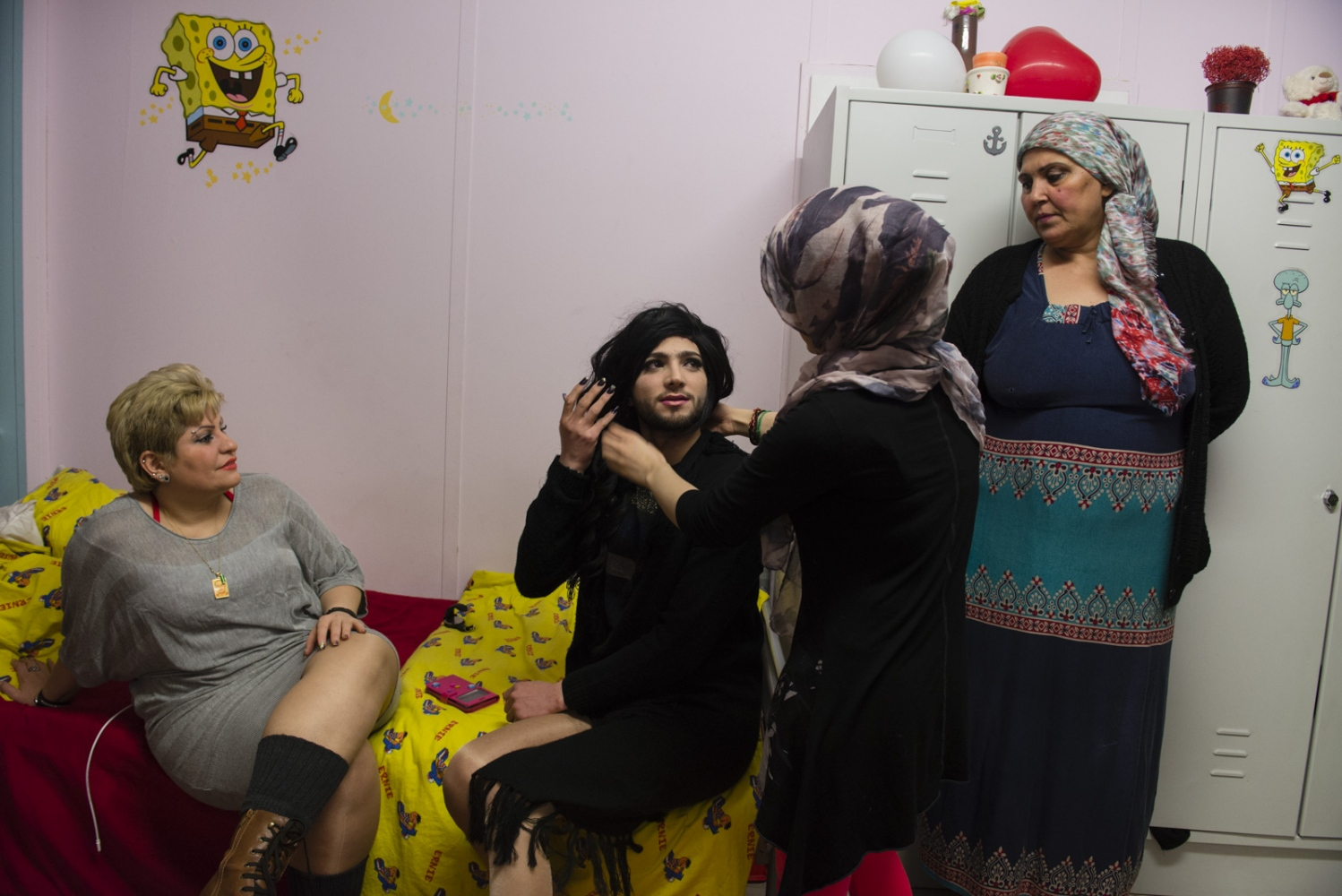BERLIN | GERMANY | 2017-02-26 | Inside a refugee camp, three Iraqi women, help Ward (22) to dress up as a drag queen for a gay party. Ward (his nickname which means Rose in arabic) is from Aleppo and arrived in Germany as a refugee in 2015. He was placed in a small town in northern Germany bordering with Denmark, called Bredstedt, by the immigration service but being a gay refugee in a small German town has not been easy for him. He has been transferred to other towns twice so far.