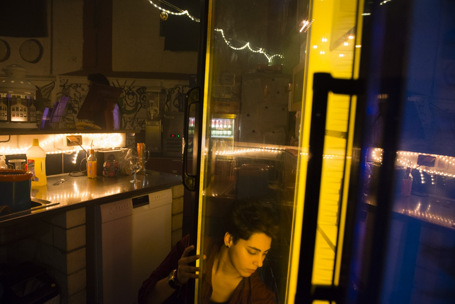 BERLIN| GERMANY | 2017-03-05 | Salwana (19) refill the beer fridge at work, a family-run bar in Berlin. She was only 13 year old when the civil war started in Syria. It took a couple of years until her hometown of Damascus was hit by war and therefore her life was impacted it. Salwana and her family fled Syria and flew into Germany in 2014 where they seek asylum. Now going to school and working at a bar part time, Salwana is well adopted and embraces her new home.
