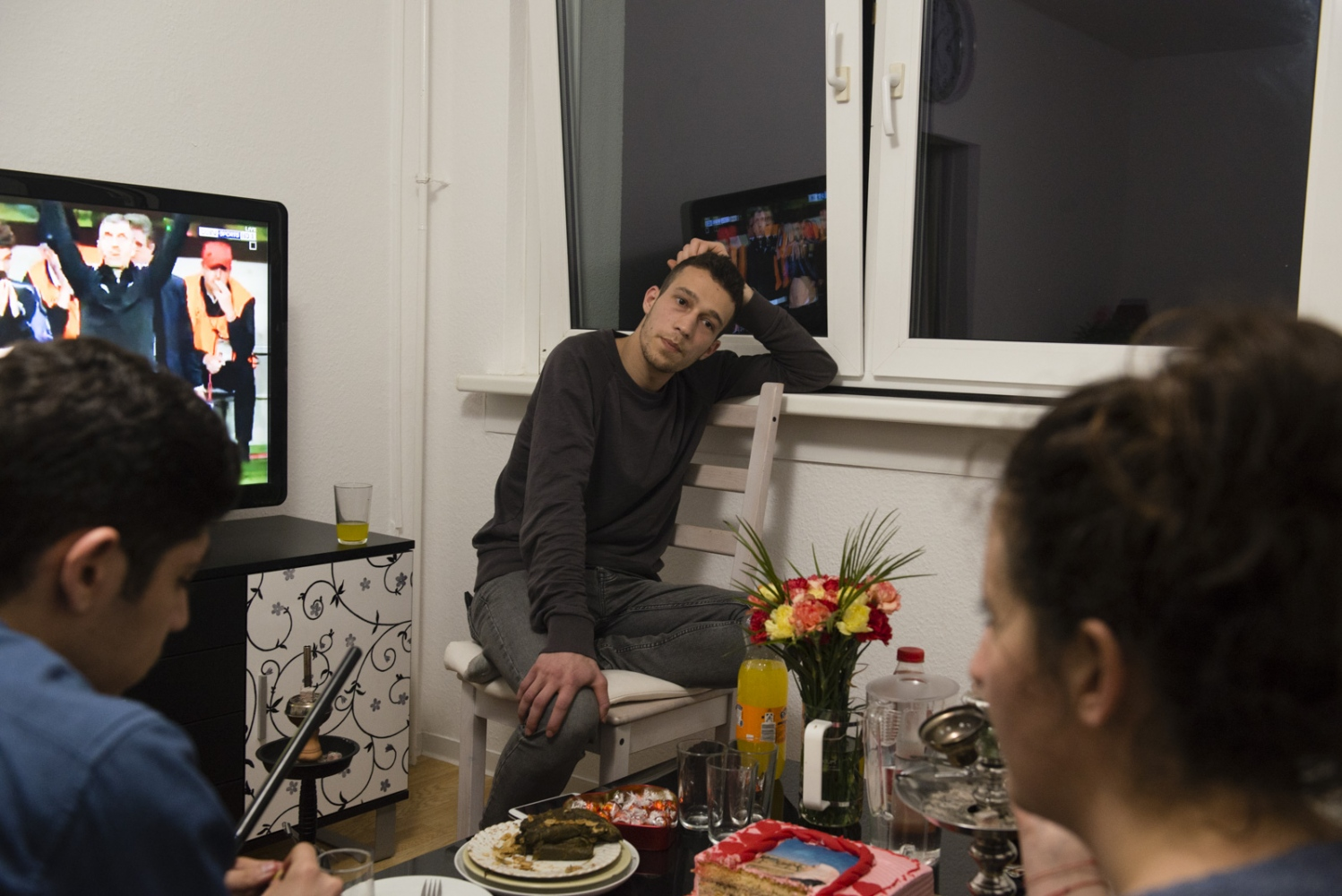 BERLIN| GERMANY | 2017-04-13 | Cheering for the German team of Bayer Munich, Amjad (23) smokes hooka at a monthly gathering where Syrian refugees and their German friends come together and socialize over tea, coca cola and hooka.