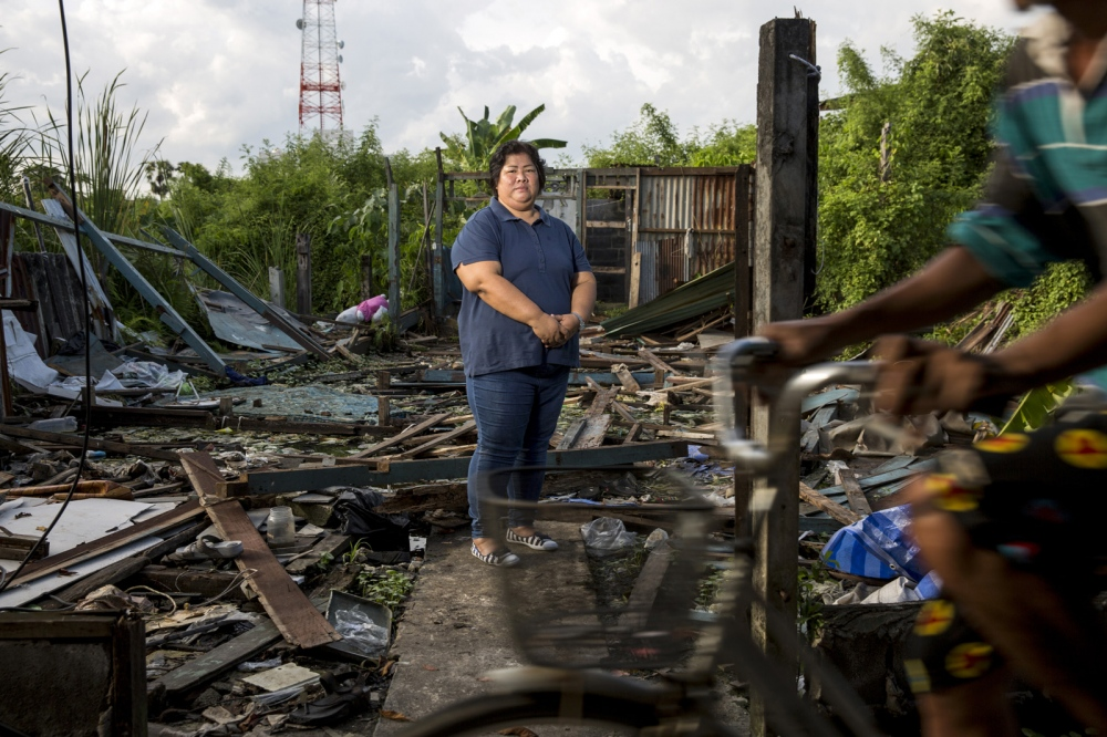 Nutchanart Thanthong stands in the remains of a destroyed house in the small slum community fighting forced evictions. For over 20 years she has assisted communities in and around Bangkok who are facing eviction as part of the Four Regions Slum Network. Samut Prakan, Thailand