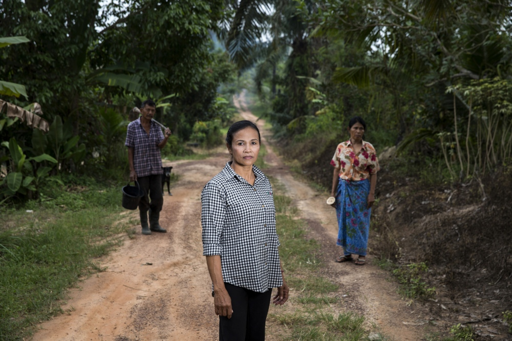 Asane Rodphol stands on the track that runs through her community of Nam Daeng in Surat Thani Province. Behind her stand other members of the community which is supported by the Southern Peasants Federation of Thailand as it faces legal threats and eviction. Surat Thani, Thailand