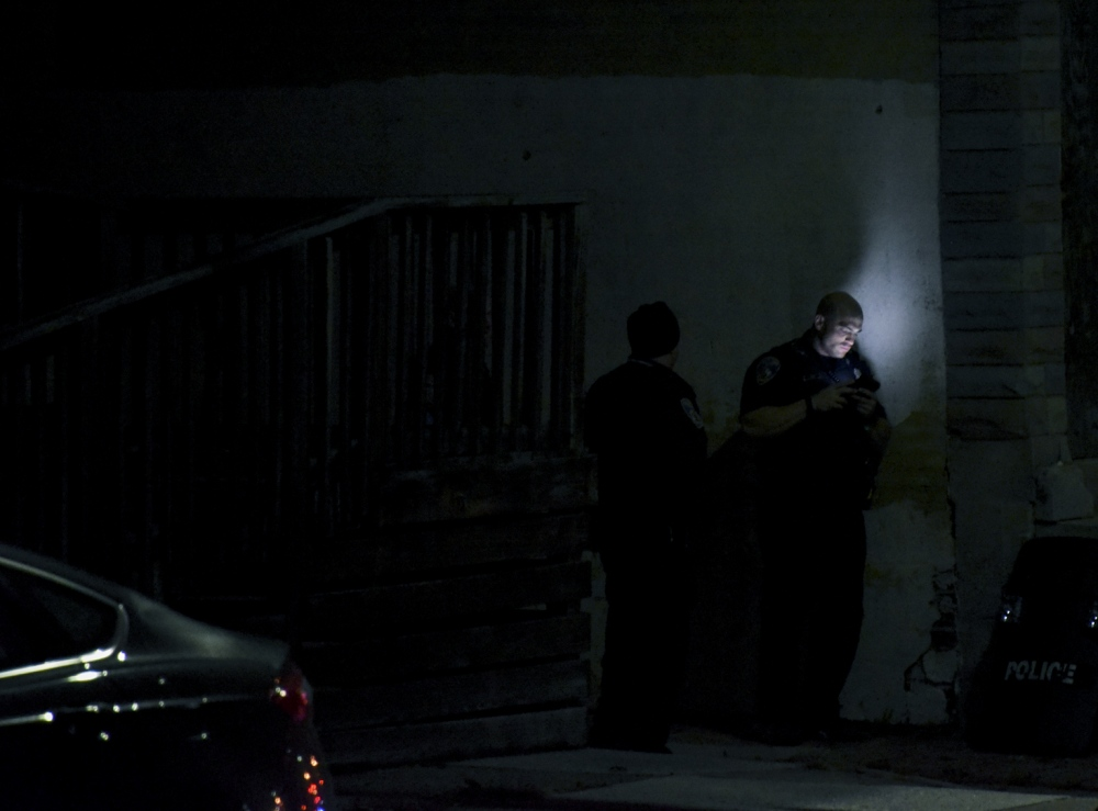Photography image - A Baltimore City Police officer checks his cell phone while on a search for a gunman in West Baltimore who shot and killed an officer earlier that day.
