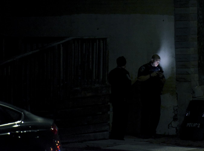 A Baltimore City Police officer checks his cell...