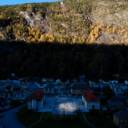 Rjukan, Norway, 2017. The town of Rjukan, 3400 inhabitants, was founded between 1905 and 1916 and is located in a narrow valley 3 hours north-west from Oslo. During the winter months, from September to March, the village is completely in the shade, as the sun, covered by the 1800 meters high peak Gaustatoppen, can't illuminate it. In 2013, a local artist named Martin Andersen, submitted to the community the intention to put on the top of the mountain three huge solar-powered mirrors able to reflect the sun light on the town square.