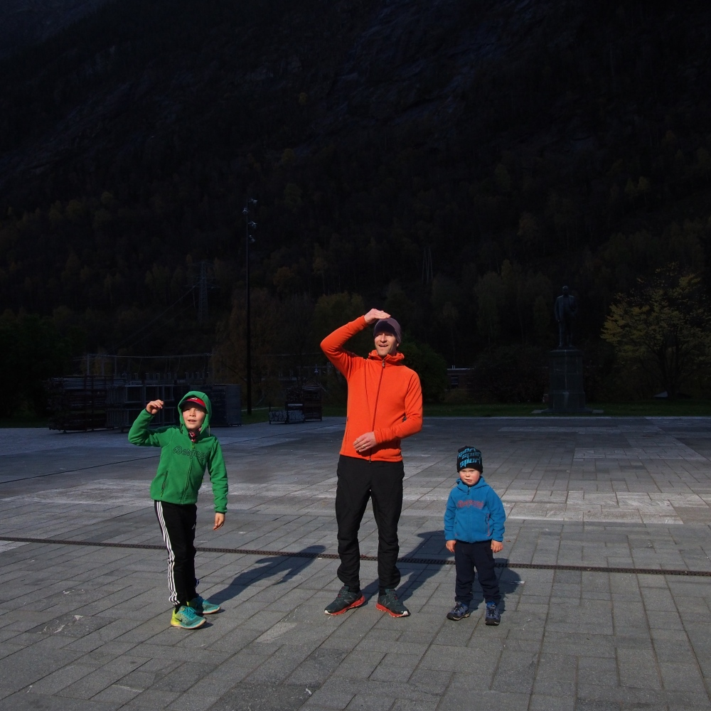 Rjukan, Norway, 2017. A family is looking toward the light reflected by mirrors, covering their faces to protect their eyes.