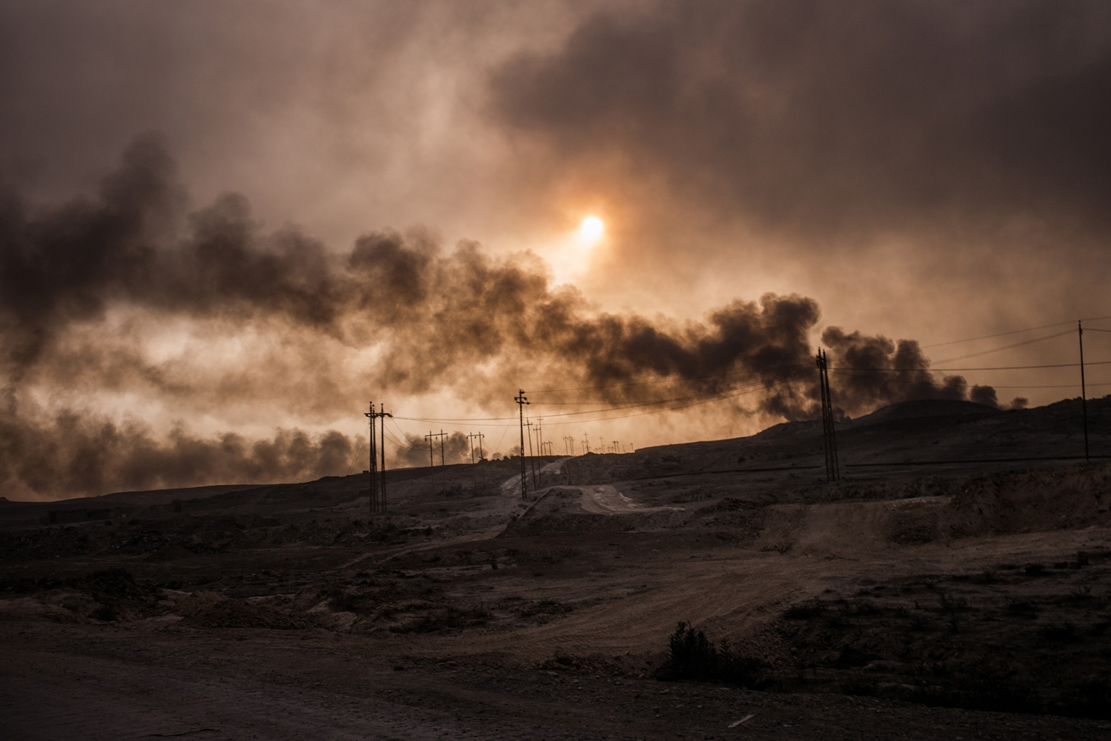 Oil wells burn in Qayyarah, Iraq, November 2016. Many streets and neighborhoods in Qayyarah look apocalyptic, with oil residue covering all surfaces, turning small streets into muddy oil slicks, yet children can still be seen everywhere playing outside. Dozens of oil wells were set on fire as ISIS fighters retreated from the Iraqi Army in August, before the start of the Mosul offensive last month. The oil from Qayyarah provided a huge source of income for ISIS to help finance its activities. Many civilians stayed in their homes during the fight to retake the town and remain there today despite the months of smoke clouds hanging over the town.