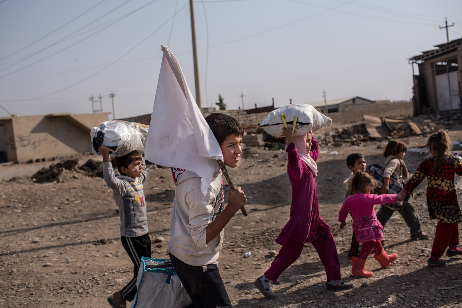 A boy carries a white flag indicating he is not a combatant while feeding from Mosul as Iraqi forces pushed deeper in the ISIS territory, near Gogjali, Iraq, November 2016. Over 100,000 civilians have fled from Mosul since the start of the offensive in October 2016 to retake the Iraqi city back from the hands of ISIS, which has controlled it for over two years.