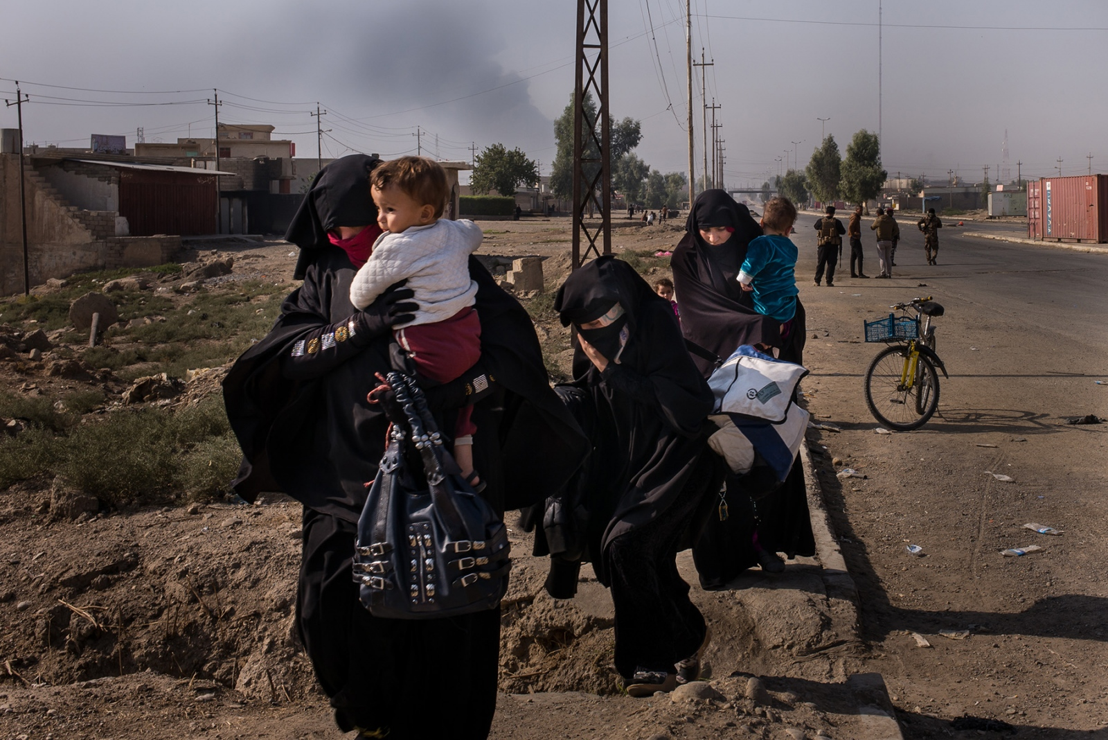 Women flee from fighting in Mosul carrying their children and the few belongings they could take near Gogjali, Iraq, on the outskirts of ISIS's so-called Caliphate, where women were forced to wear the full face veil (niqab) in addition to wearing gloves to cover up all skin except the eyes.