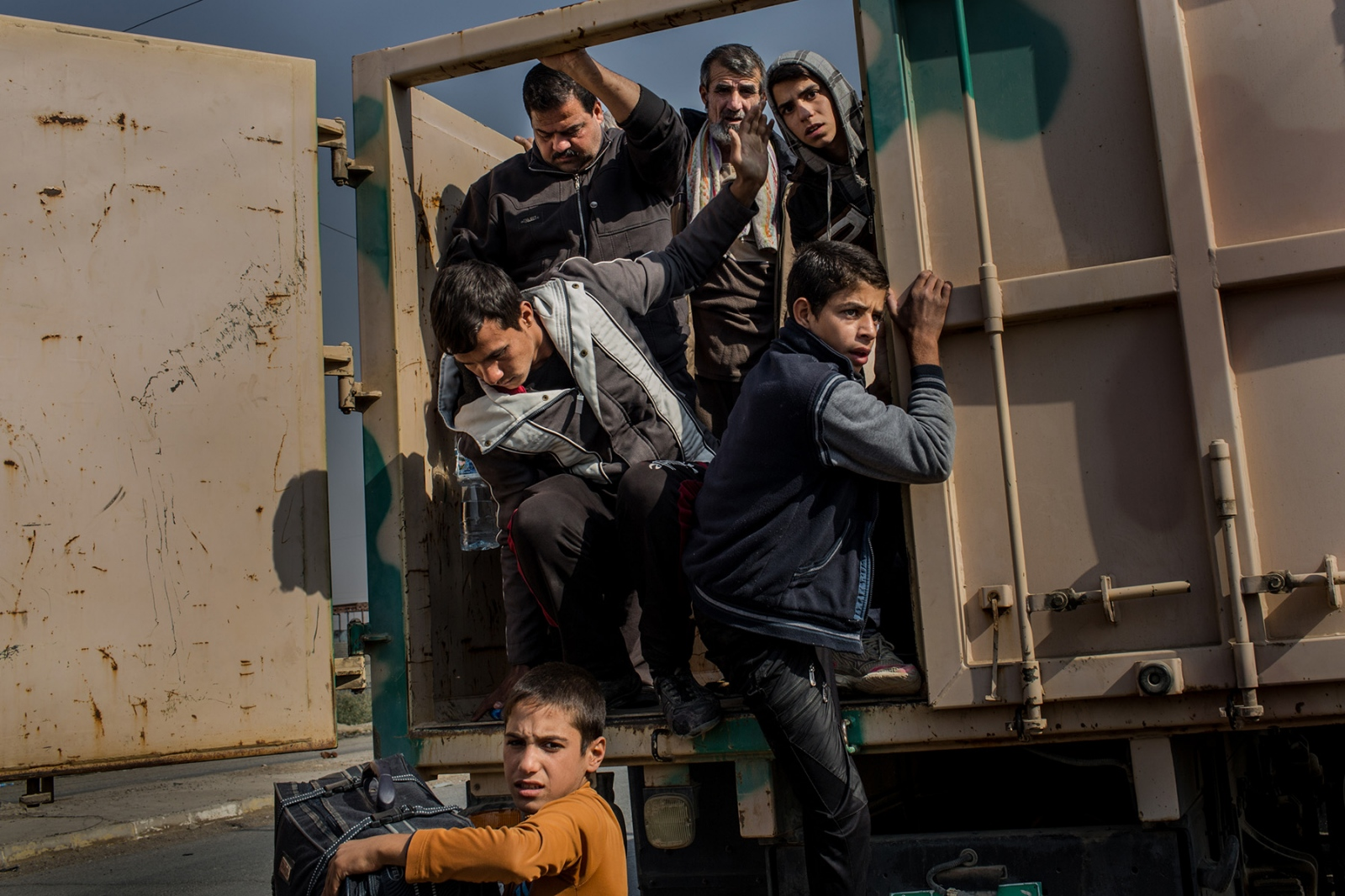 A convoy of men fleeing from Mosul are taken off a truck to be searched and checked against a wanted list of suspected ISIS fighters near the town of Gogjali, Iraq, November 2016. Iraqi security forces have been conducting rigorous checks on fleeing civilians to ensure they were not collaborating with ISIS, but their methods of interrogation have drawn criticism from rights groups such as Amnesty International, saying that torture and executions of Sunnis is in part due to revenge attacks.