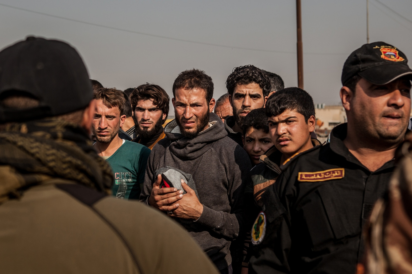 Men wait to have their IDs returned to them following security checks against wanted lists of ISIS fighters in Gogjali, Iraq, a few kilometers from Mosul, November 2016. Various checkpoints have been set up on the road out of Mosul to ensure that those fleeing amongst civilians are not ISIS members.