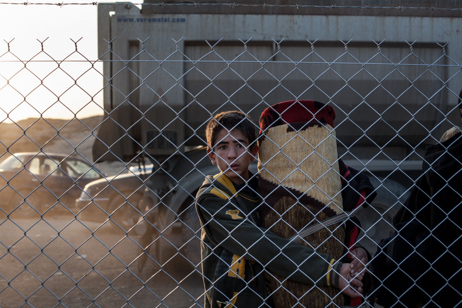 A boy, newly arrived at the Hassan Sham IDP camp, looks through the fence after having fled fighting in Mosul, Iraq. November 2016.