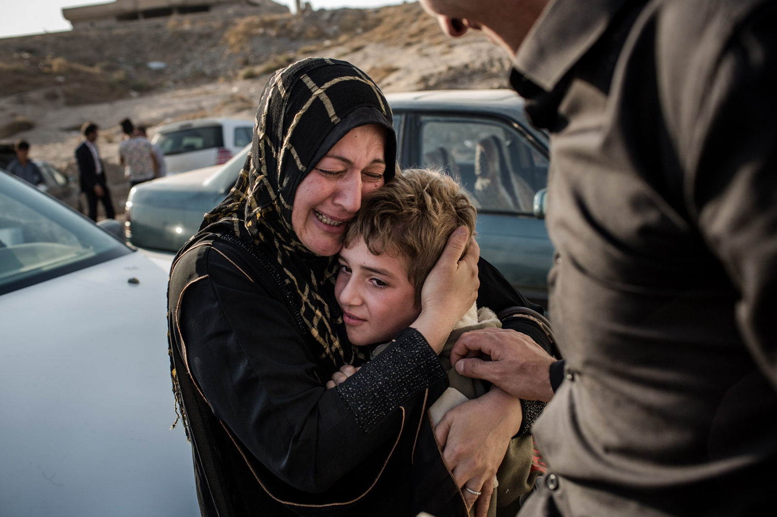 A woman cries while she cradles her son Laith, whom she had not seen for two years as they were finally reunited at the Hassan Sham camp for internally displaced persons near Mosul, Iraq, on November 7, 2016. Laith was trapped in Mosul when it fell to ISIS in 2014. Laith's mother, who could not go back to their home in Mosul, was forced to stay outside of ISIS territory, longing for the day to see her son again.