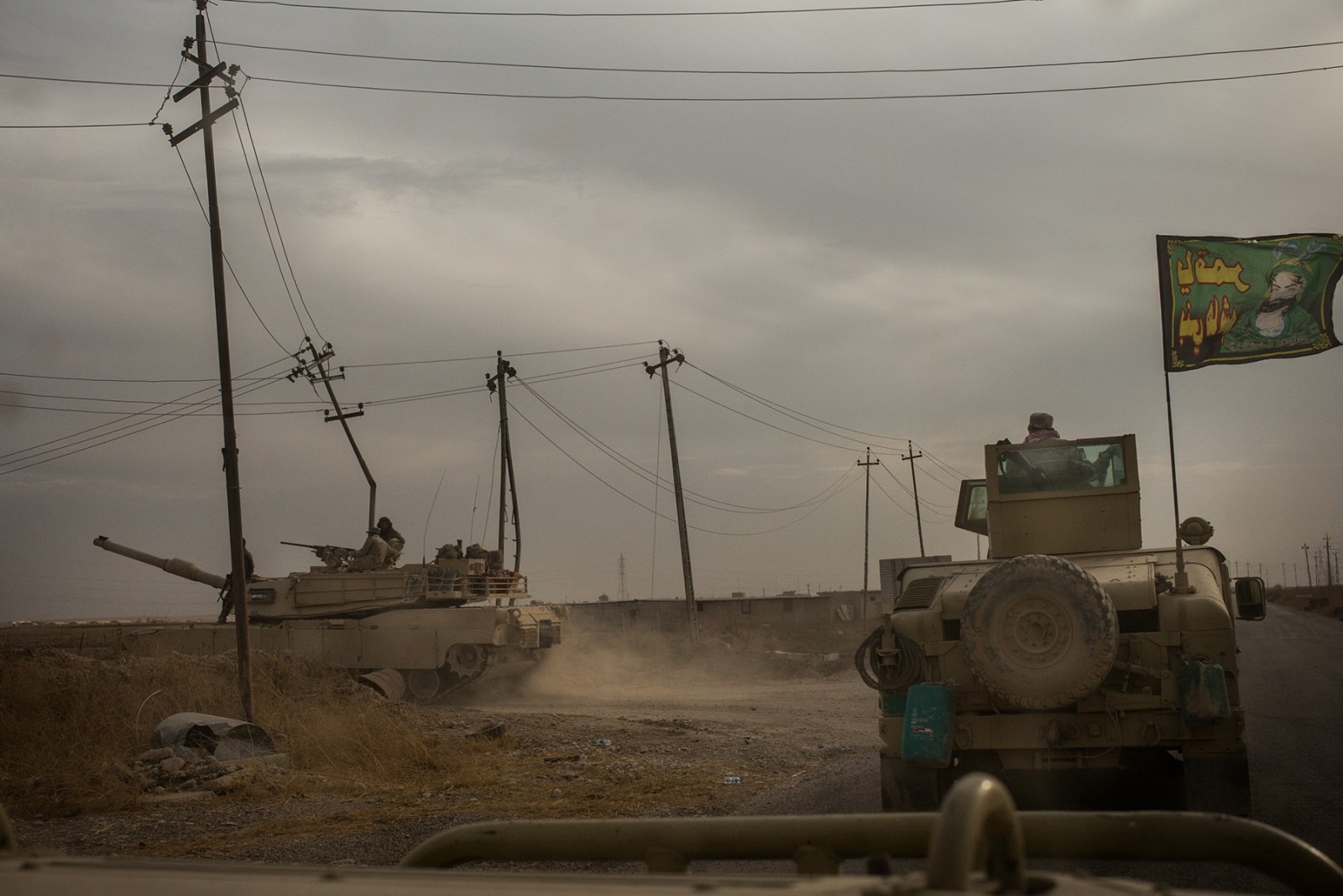 Fighters with the Popular Mobilization Units, who are predominantly Shia, drive in armored vehicles near Mosul, Iraq. November 2016.