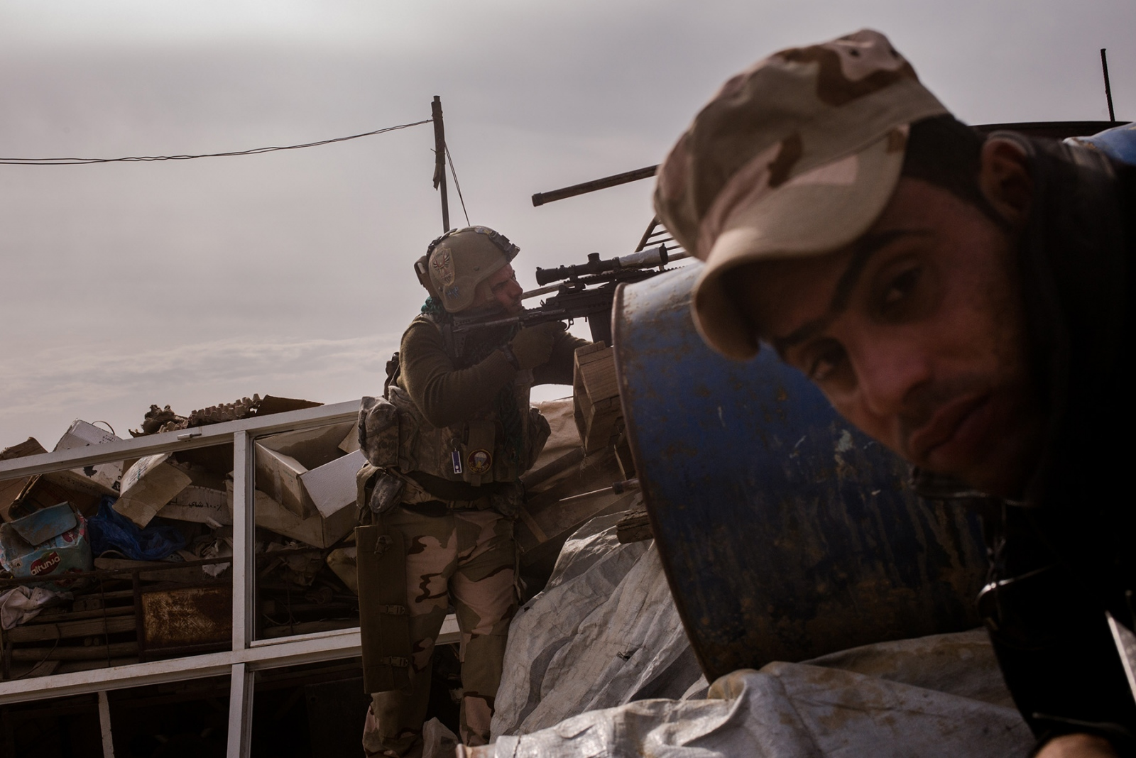 A soldier of the Iraqi Army's Ninth Division aims towards ISIS positions in the Entisar neighborhood of Mosul, Iraq, on Tuesday, November 15, 2016. The presence of so many civilians inside the city has slowed the offensive to retake Mosul, which began in October 2016, against ISIS in taking back the so-called capital of their caliphate. For the civilians who remain, they face food shortages and the constant threat of being caught in the crossfire.