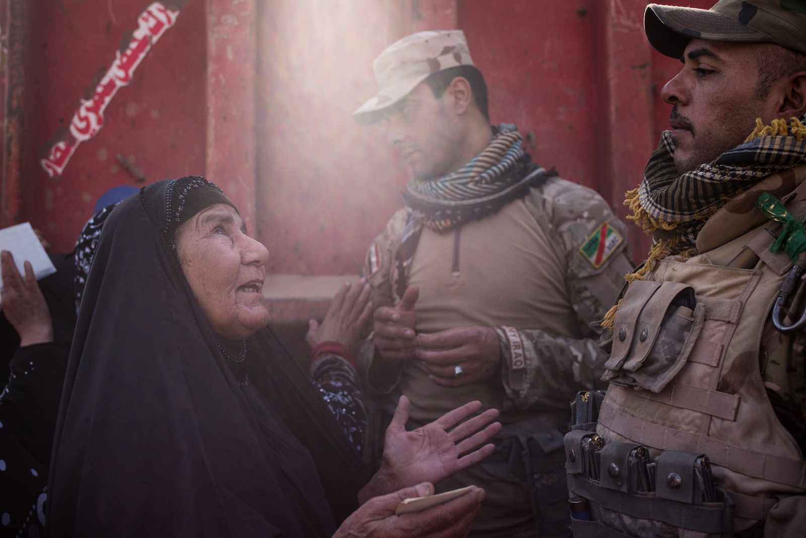 An elderly woman pleads with a soldier of the Iraqi Army's Ninth Division to give local civilians food aid in the Entisar neighborhood of Mosul, Iraq, just meters from the frontline where Iraqi forces are in engaged in fighting with ISIS in Hay Salam, November 2016. A helicopter strafed nearby buildings where ISIS snipers were positioned. 1 million civilians are estimated to be in Mosul, where many have been prevented from leaving by ISIS, while others have remained in their homes rather than fleeing to internally displaced persons camps. The presence of so many civilians inside the city has slowed the offensive, which began last month against the extremist group in taking back the so-called capital of their caliphate. For the civilians who remain, they face food shortages and the constant threat of being caught in the crossfire.