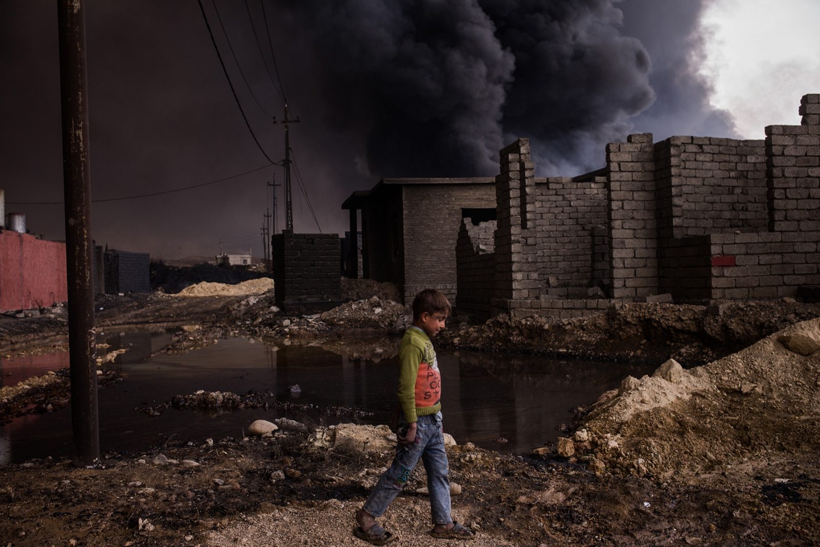 A boy walks through a street near his home in Qayyarah, Iraq, November 2016, as an oil well burns nearby. Many streets and neighborhoods in Qayyarah look apocalyptic, with oil residue covering all surfaces, turning small streets into muddy oil slicks, yet children can still be seen everywhere playing outside. Dozens of oil wells were set on fire as ISIS fighters retreated from the Iraqi Army in August, before the start of the Mosul offensive last month. The oil from Qayyarah provided a huge source of income for ISIS to help finance its activities. Many civilians stayed in their homes during the fight to retake the town and remain there today despite the months of smoke clouds hanging over the town.