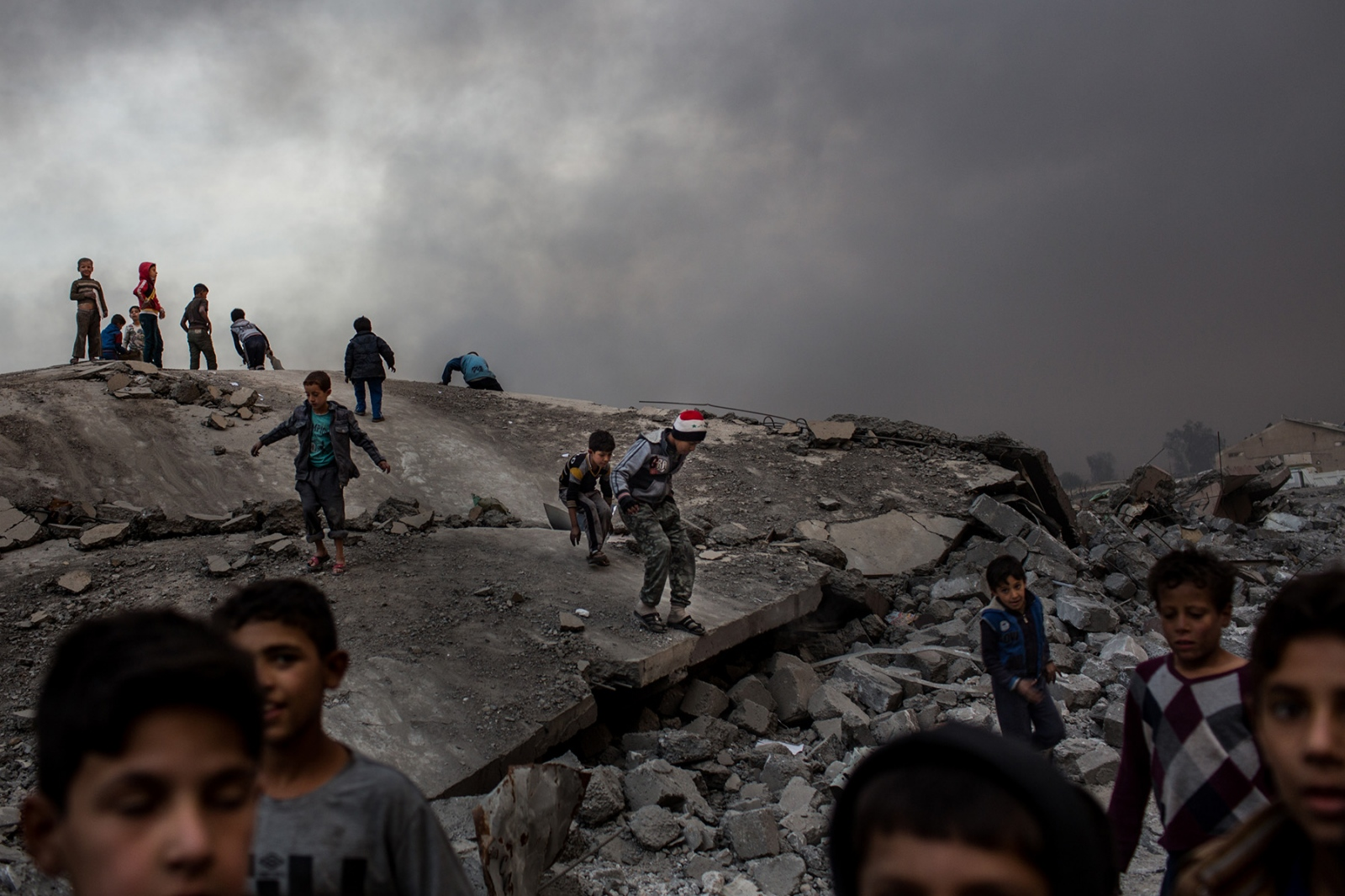 Children play on the rubble of what was once a stadium in Qayyarah, Iraq, on Wednesday, November 9, 2016, as a constant cloud of smoke hangs over the sky. The stadium, which was used by ISIS to hide their weapons stockpiles was destroyed by coalition airstrikes over the summer and oil wells were set on fire as ISIS fighters retreated.