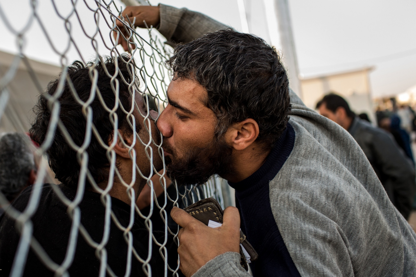 A man kisses his brother through the fence at the Hassan Shami camp near Mosul, Iraq, November 2016. The two brothers, who were separated from each other when the offensive to retake Mosul began, had not seen each other for nearly two weeks, both fearing for each others' lives as the fighting intensified. They shed tears of joy at having finally been reunited at the camp.