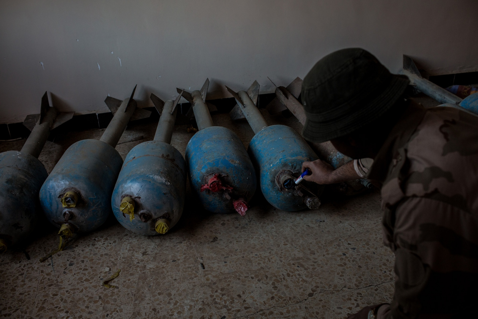A soldier with the Christian Nineveh Plains Units examines a home-made bomb manufactured by ISIS in the town of Qaraqosh, Iraq on November 8, 2016. Even after towns and villages are liberated from the extremist group, many dangers remain, including unexploded ordinances, improvised explosive devices and booby traps ISIS has left behind for enemy troops. Many bomb making factories are found in people's homes overtaken by ISIS.