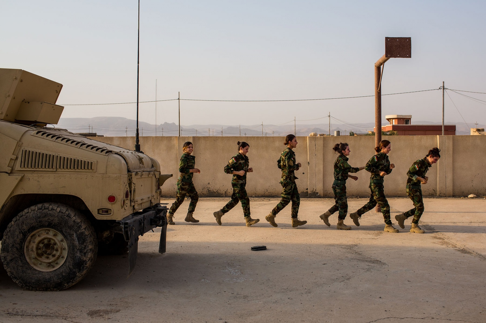 Soldiers with the Yazidi 'Sun Ladies' run laps during morning exercises at their base near Sinjar, in Kurdistan, Iraq, on Tuesday, August 30, 2016. The 'Sun Ladies', made up of several hundred Yazidi women, some who were formerly enslaved by ISIS, are attempting to fight back against the extremist group with the help of the Kurdish Peshmerga through training, funds, and arms.