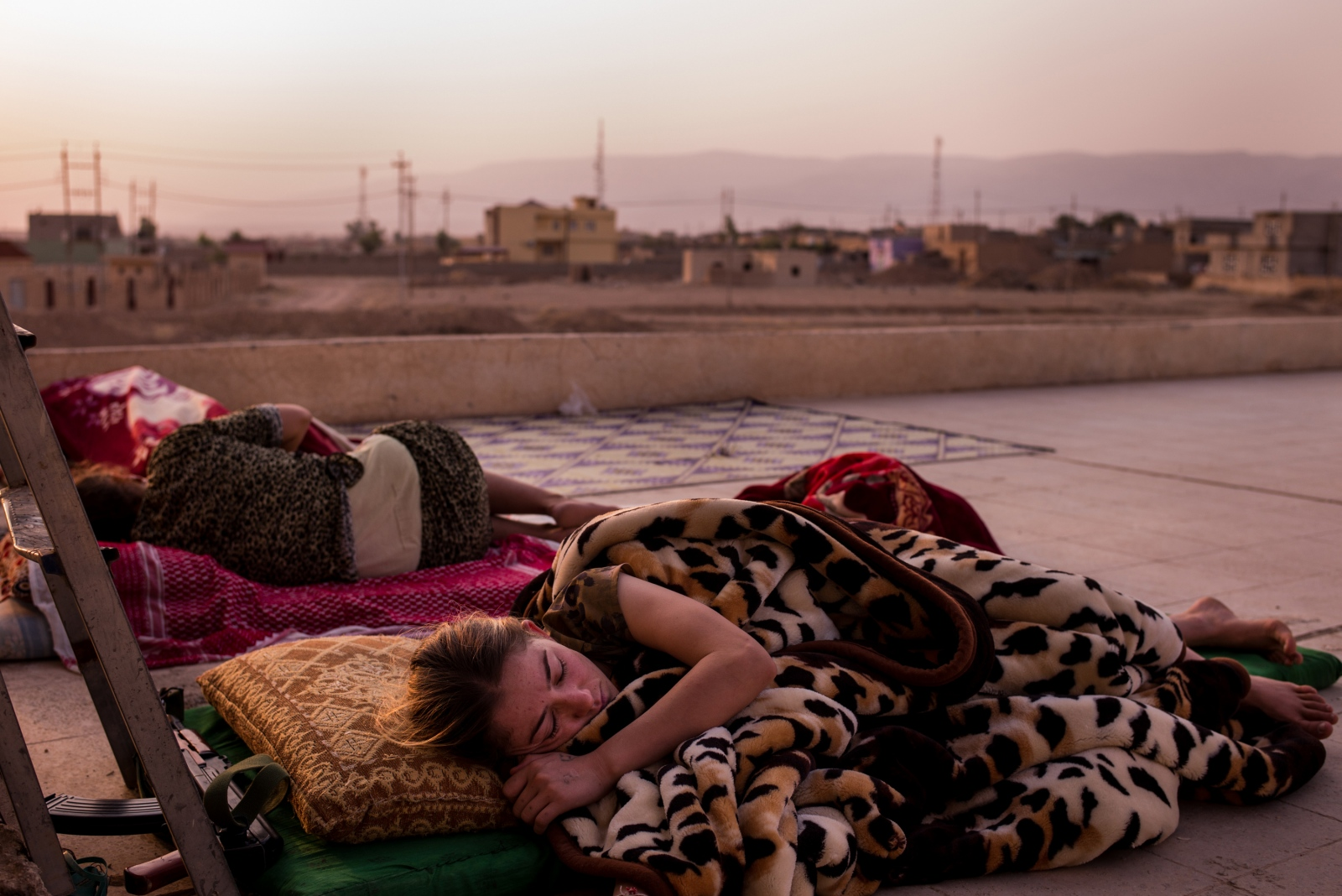 Lina, a soldier with the Yazidi 'Sun Ladies' battalion, sleeps just before dawn at their base near Sinjar, in Kurdistan, Iraq, on Tuesday, August 30, 2016. The 'Sun Ladies', made up of several hundred Yazidi women, some who were formerly enslaved by ISIS, are attempting to fight back against the extremist group with the help of the Kurdish Peshmerga through training, funds, and arms.