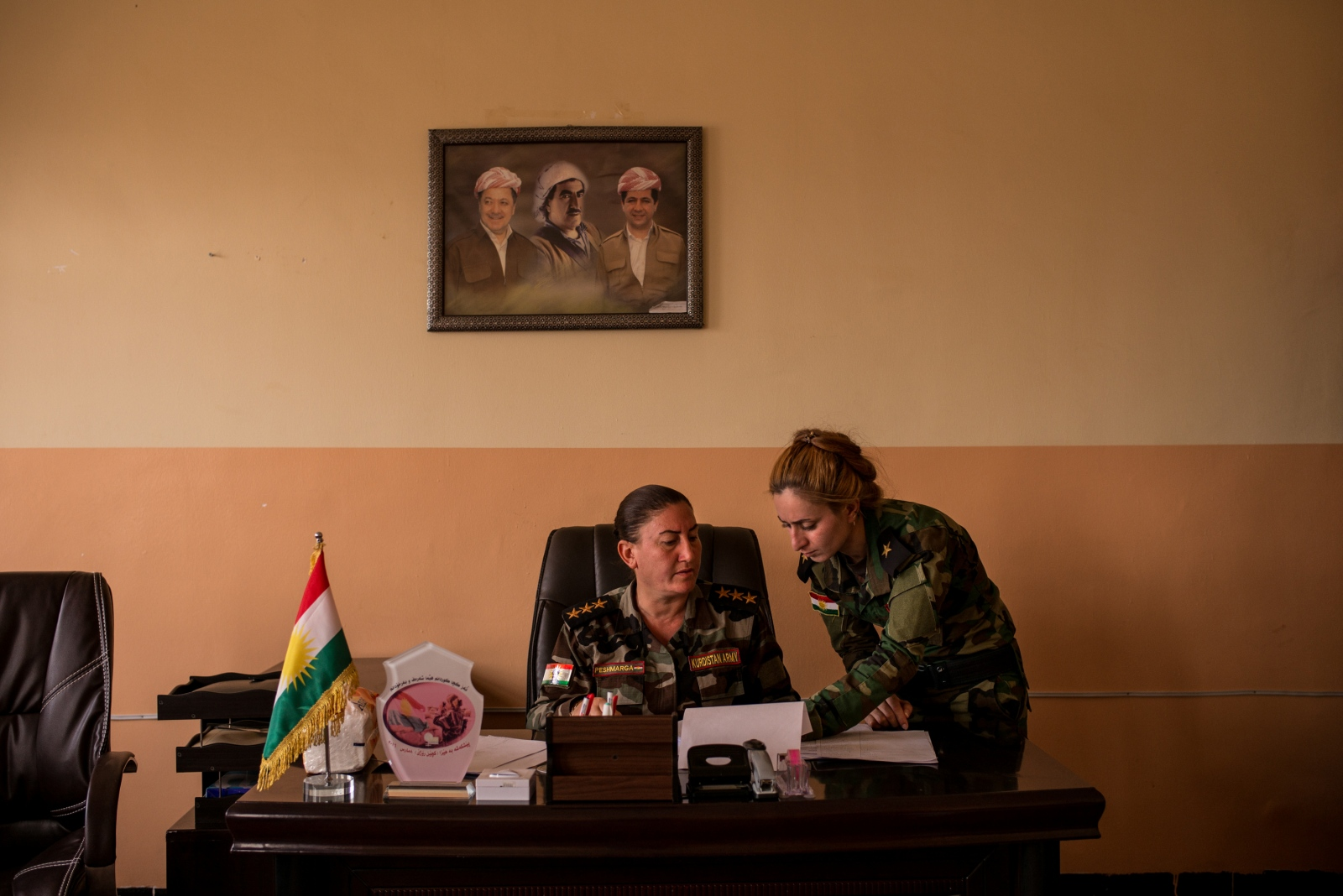 Captain Khatoon Khider, center, is assisted by her deputy in the battalion's office near Sinjar, in Kurdistan, Iraq on Tuesday, August 30, 2016. Above Captain Khider is a poster depicting the Barzani family, including Masoud Barzani (left) the leader of Iraqi Kurdistan Region.