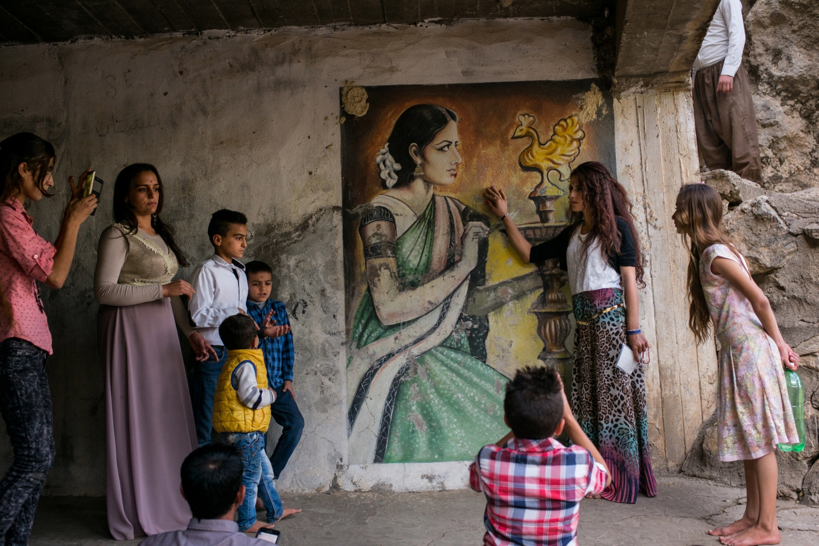 Visitors take pictures by the mural of the Peacock Angel at the temple in Lalish, Iraqi Kurdistan on November 11, 2016.