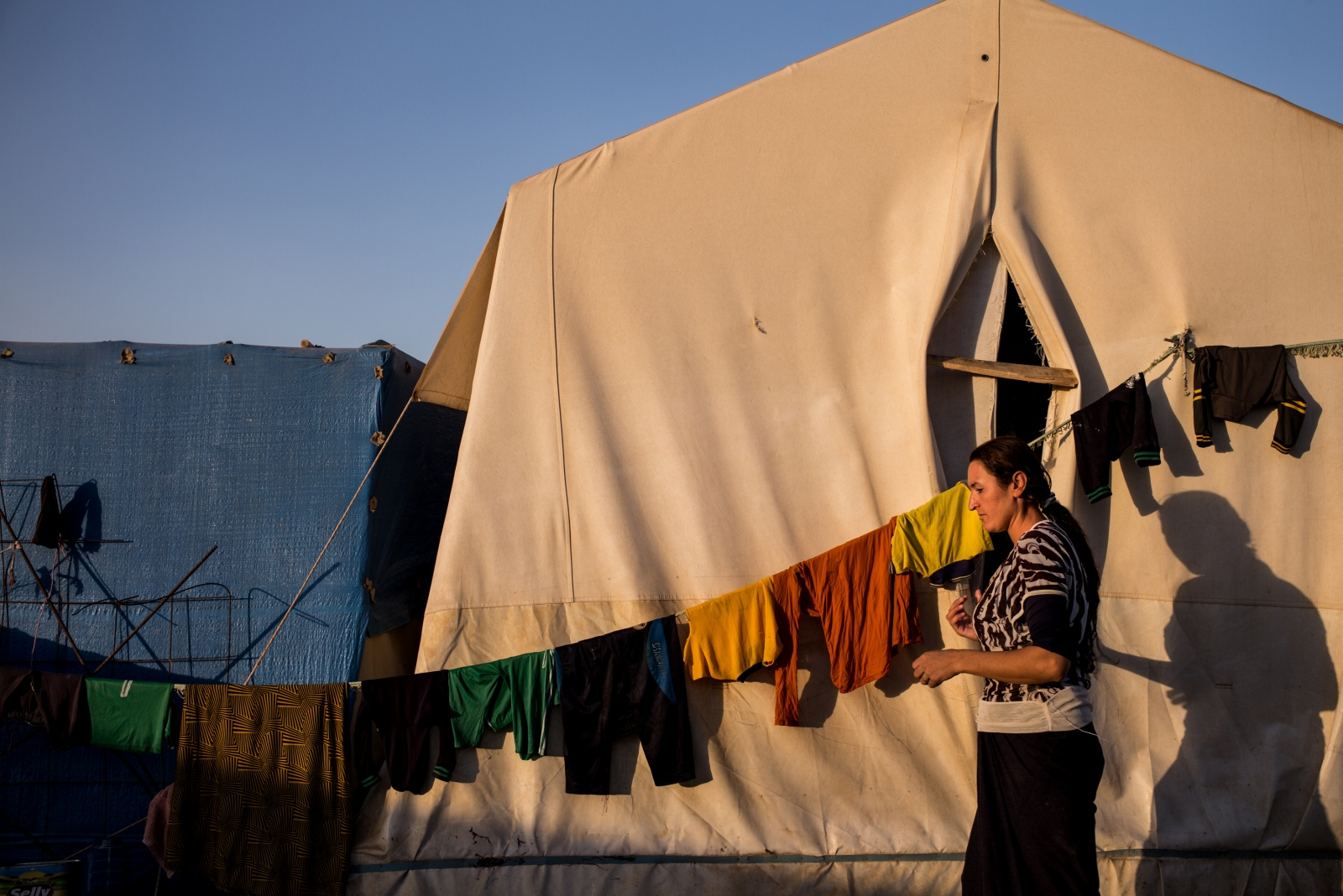 A Yazidi woman hangs laundry outside her tent at the Shariya camp for internally displaced persons near Dohuk in Kurdistan, Iraq, on Thursday, September 1, 2016. Shariya is host to nearly 19,000 Yazidis who fled from Sinjar two years ago during the ISIS onslaught.