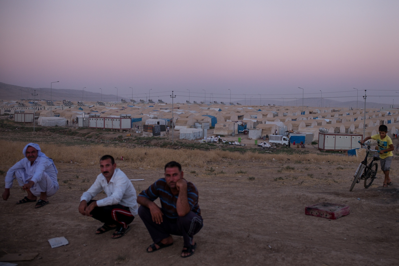 Yazidi men sit atop a hill overlooking the Shariya camp for internally displaced persons near Dohuk in Kurdistan, Iraq, on Thursday, September 1, 2016. Shariya is host to nearly 19,000 Yazidis who fled from Sinjar two years ago during the ISIS onslaught.