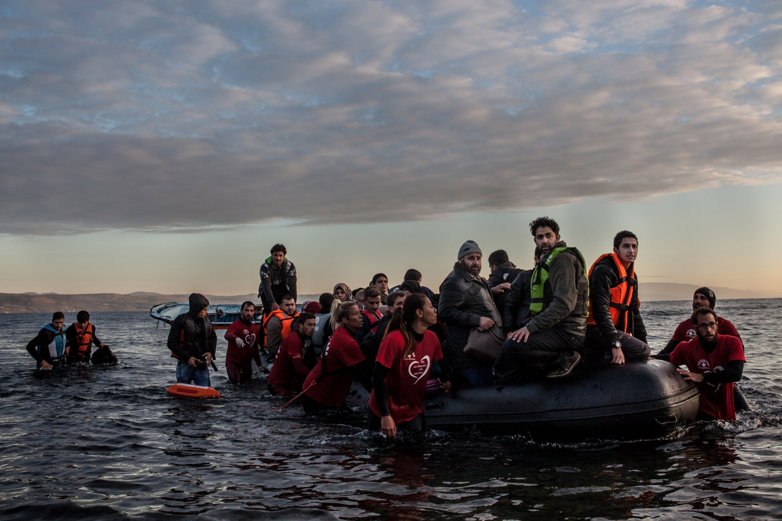 A boat filled with refugees and migrants, mostly from Syria, arrives on the shores of Lesbos, Greece, after crossing the Aegean Sea from Turkey on December 4, 2015.