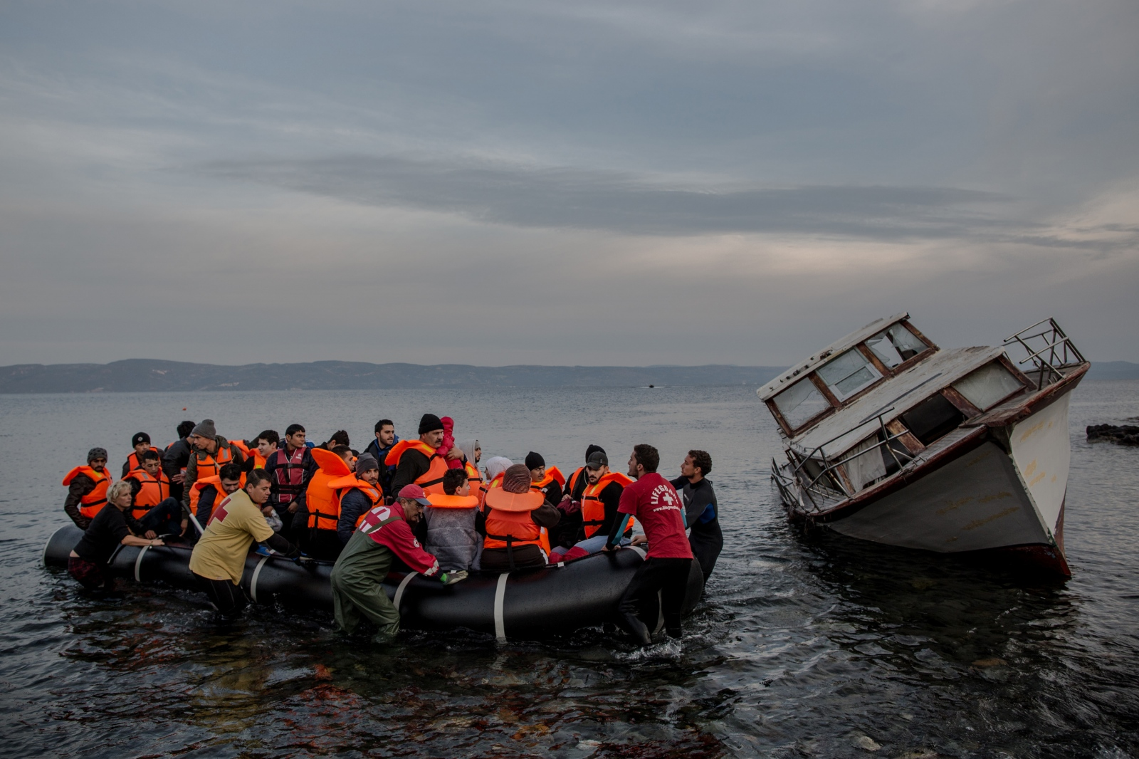 A rubber dingy, packed with refugees mostly from Syria, is assisted to shore in Lesbos, Greece, on November 16, 2015, after having crossed the Aegean Sea from Turkey. Nearby is a small wooden boat previously used by other refugees arriving in Greece.