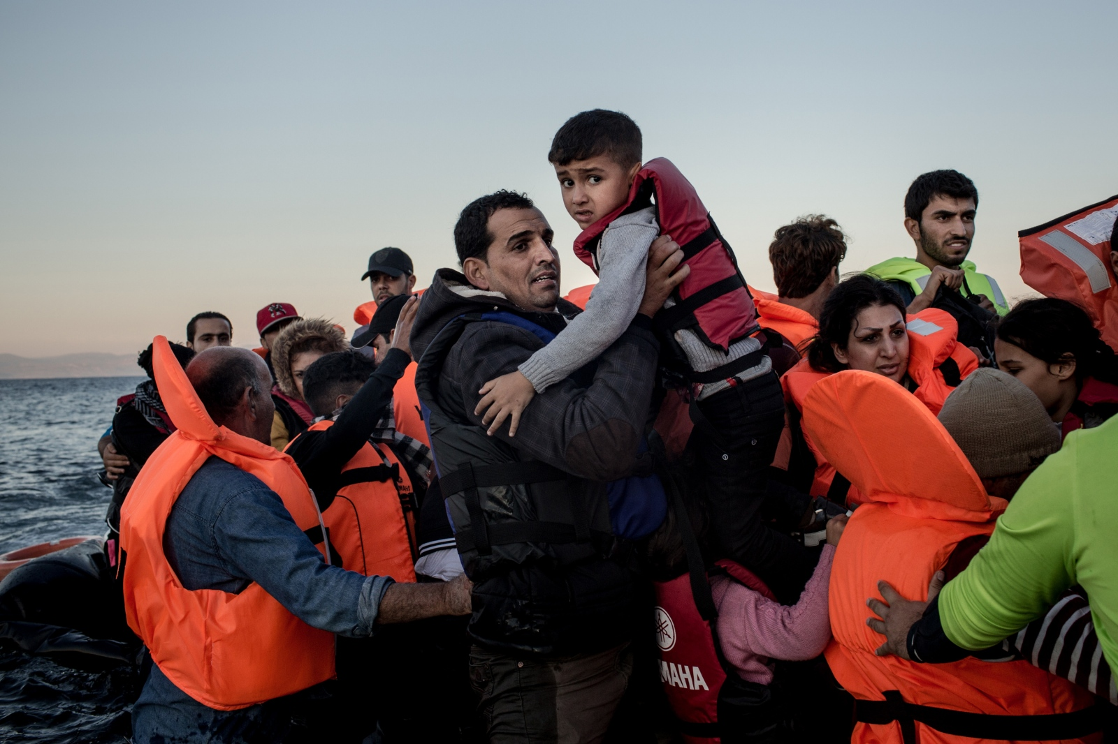 A father carries his son off a rubber dinghy after arriving on the island of Lesbos, Greece, on November 12, 2015. The roughly 1.5 hours journey across the Aegean Sea, on a clear day, costs from anywhere between $900-$3000 per person paid to traffickers on the Turkish side.