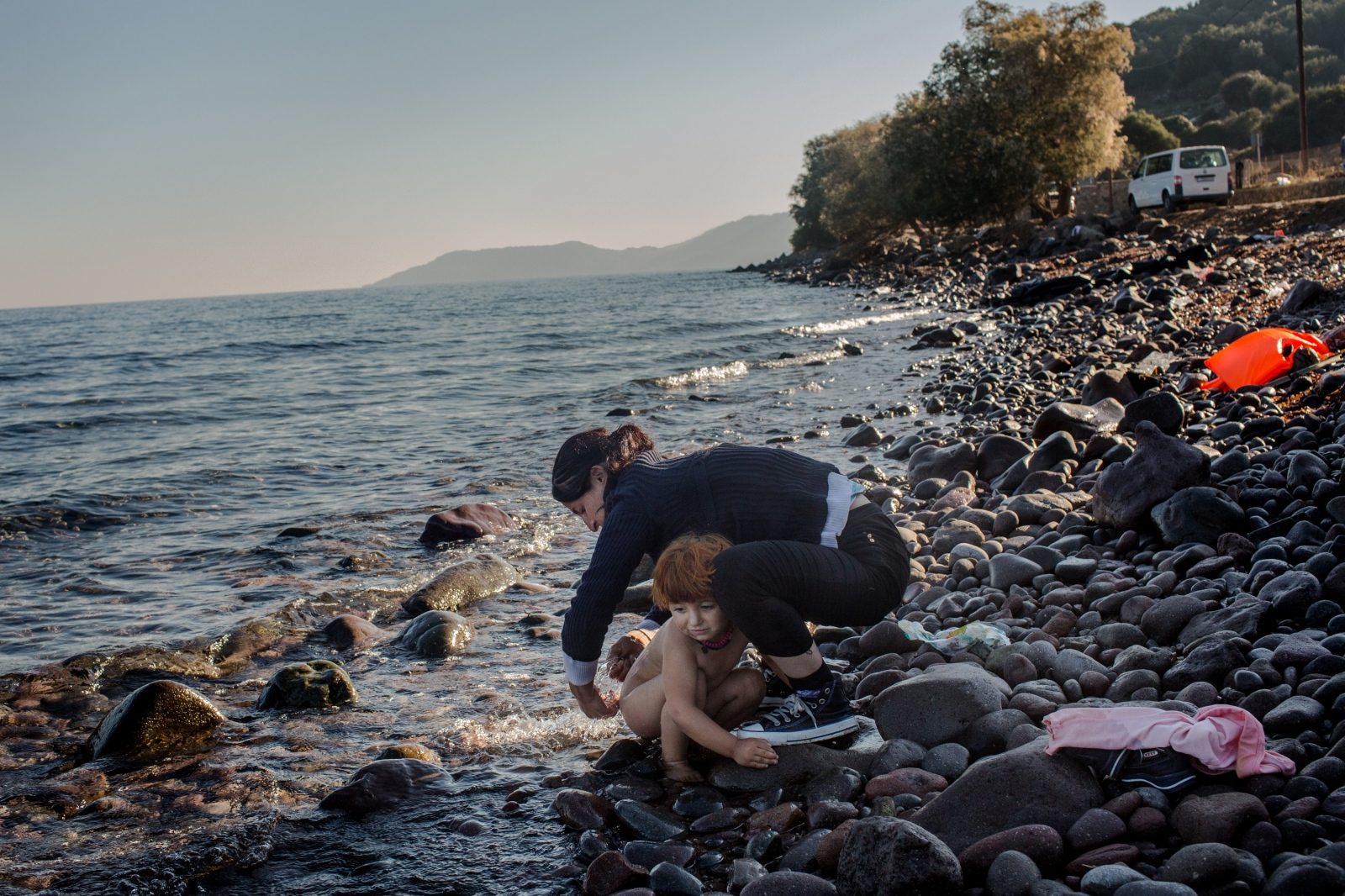 A Yazidi refugee washes her daughter in the sea shortly after arriving on Lesbos, Greece, on November 13, 2015. After a long journey, the toddler was badly in need of a wash and clean diapers.