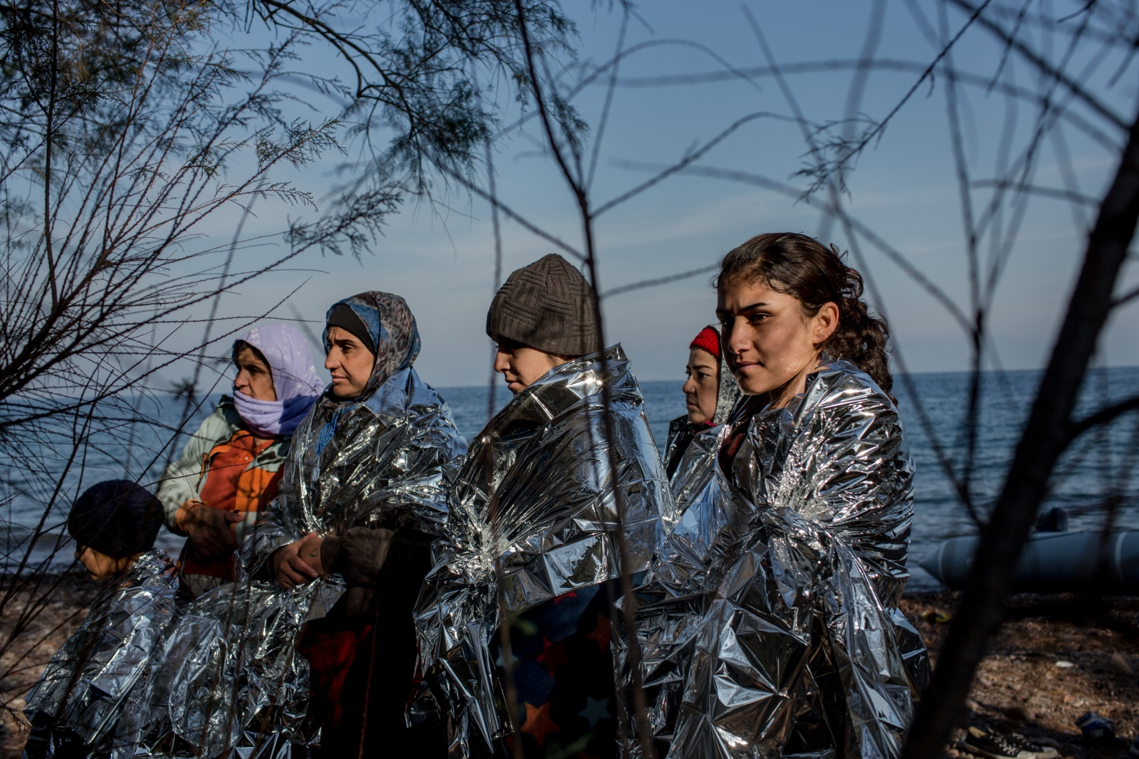 Kurdish refugees warm themselves on the beach shortly after arriving on the shores of Lesbos, Greece, after crossing the Aegean Sea from Turkey on December 8, 2015.