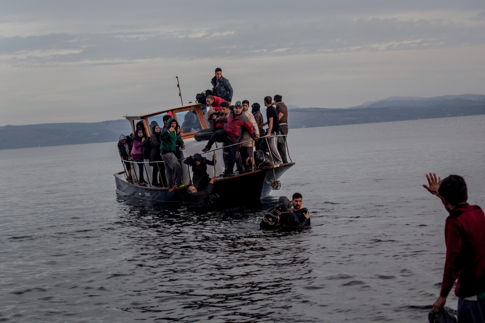 Volunteers attempt to assist a small wooden boat, packed with refugees, to shore in Lesbos, Greece, on November 16, 2015. The boat cut its engine about 50 meters from the shore without a clear reason. After all of the refugees had alighted from the boat, the engine was restarted and began making its way back to Turkey. It was discovered that the Turkish smuggler remained hidden on board to save himself for the return back to Turkey.