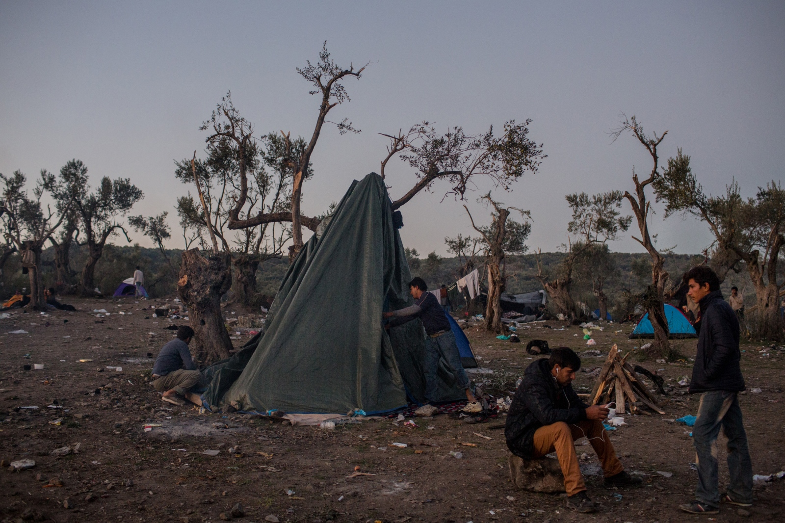 Refugees prepare to camp in the open near a registration center at the Moria transit camp in Lesbos, Greece, on November 13, 2015.