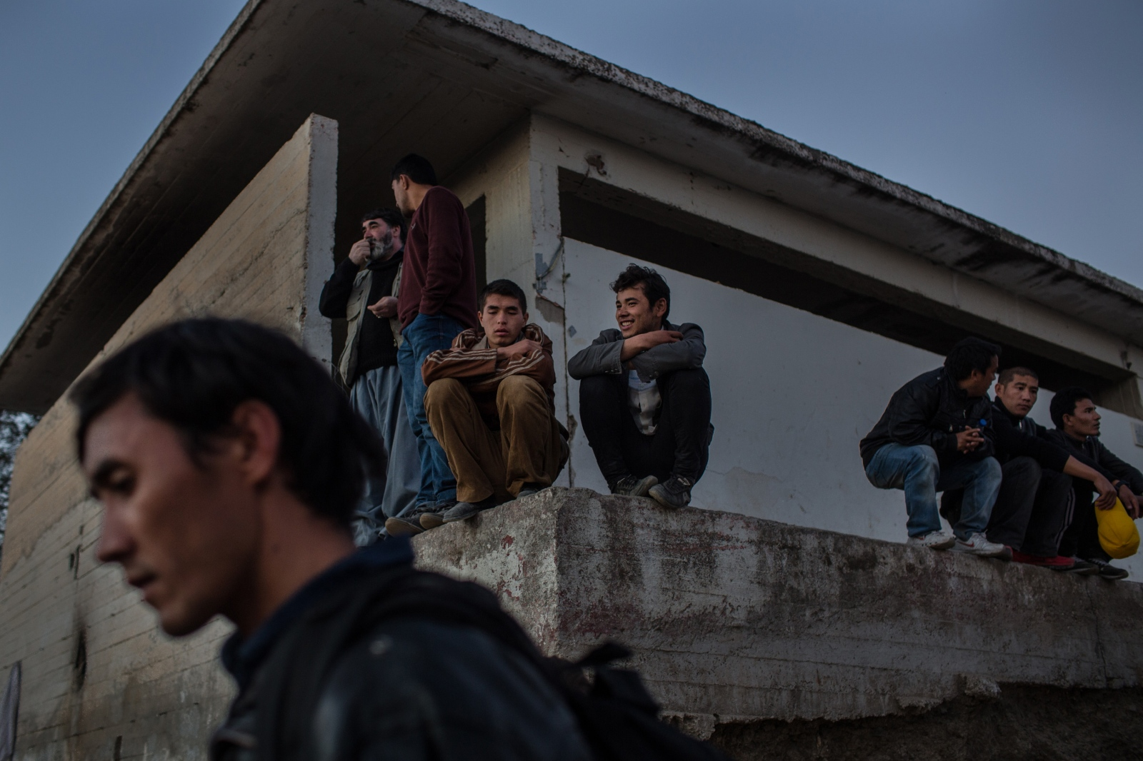 Refugees and migrants from Afghanistan and Syria wait for registration numbers at the Moria transit camp in Lesbos, Greece, on November 16, 2015.