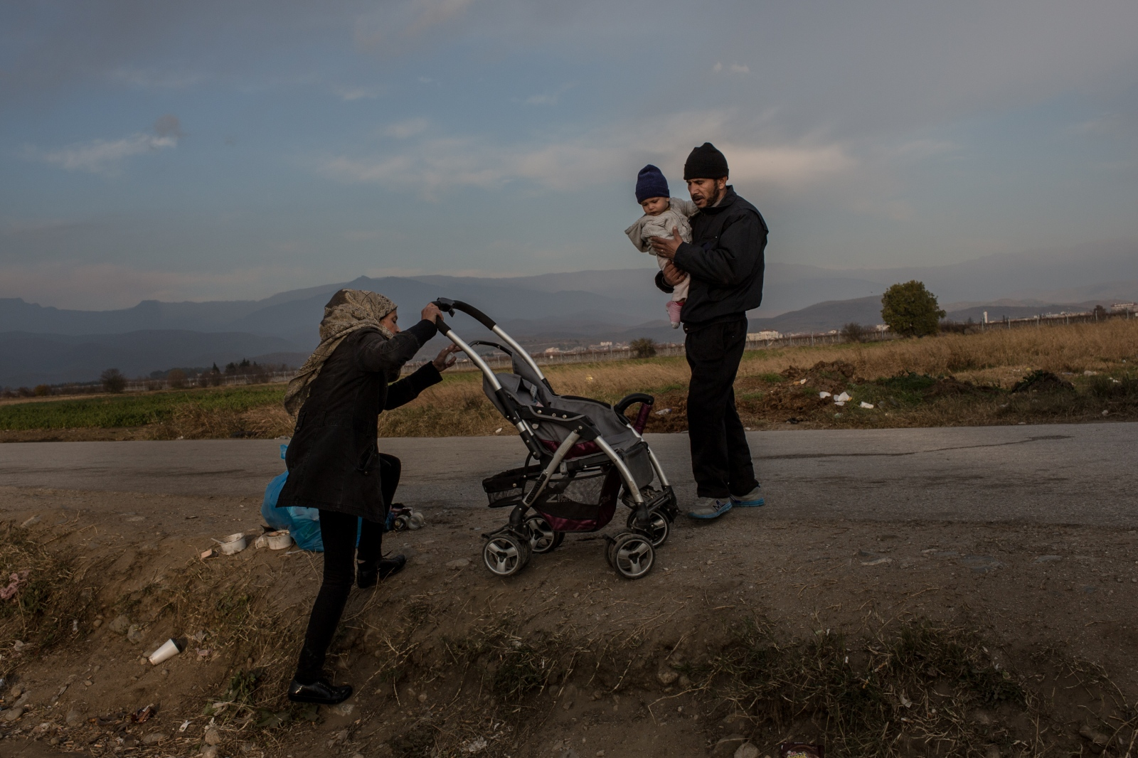 A family salvages a baby carriage near the border between Greece and the Former Yugoslav Republic of Macedonia on December 10, 2015. The previous day, a makeshift camp there with migrants from Morocco, Bangladesh, Iran, Pakistan, and elsewhere - which had been occupied for weeks - was cleared by the Greek police as Europe turns back those who are not specifically fleeing war. Refugees from Syria, Iraq, and Afghanistan are being permitted through to continue the route to Western Europe, whilst other nationalities are being directly transferred back to Athens.