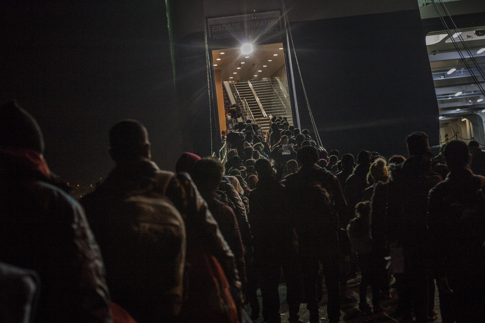 Hundreds of refugees and migrants wait to board a ferry from Mytilini, Lesbos, to Athens, after receiving their registration papers on December 8, 2015.