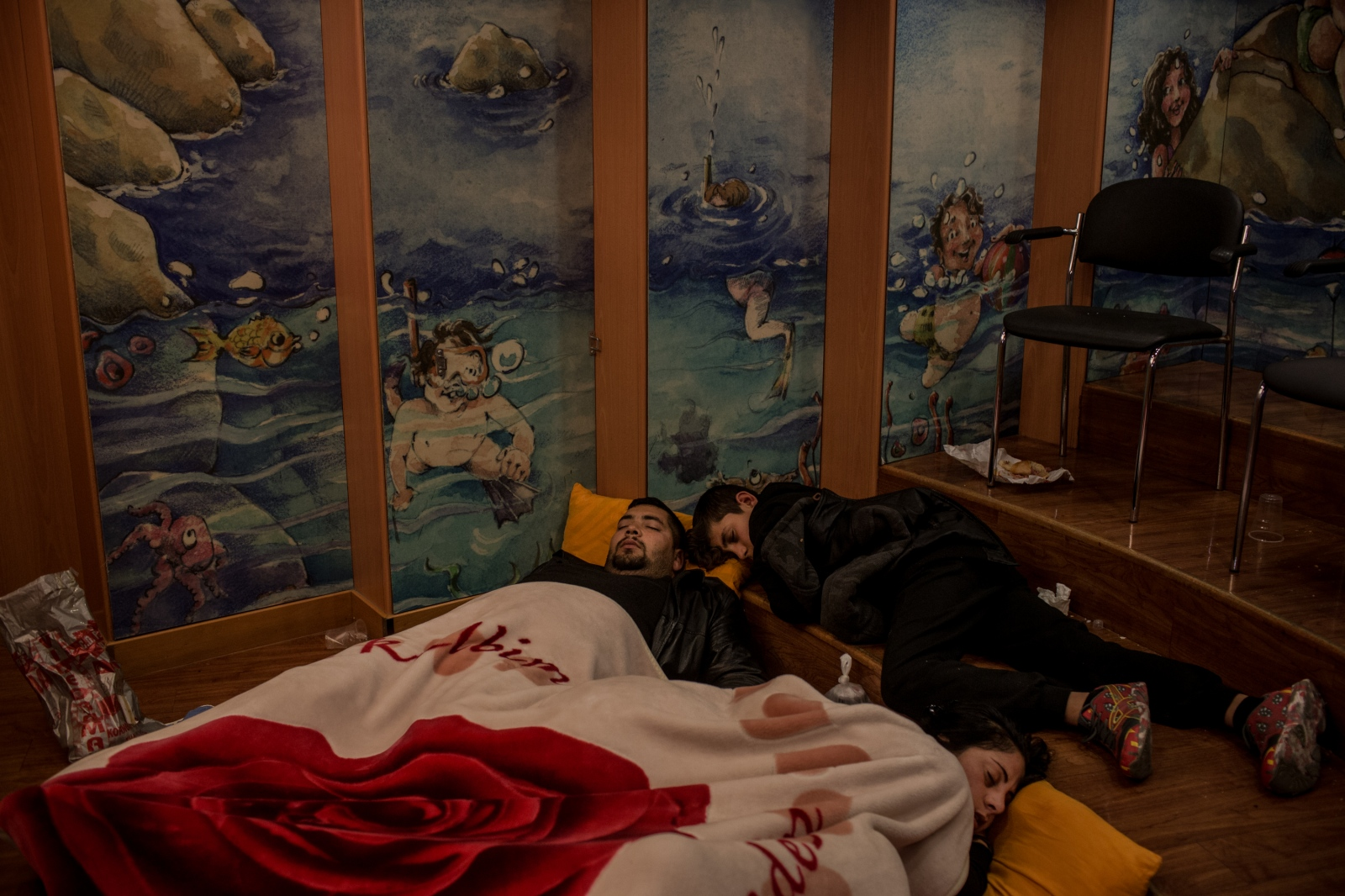 A family sleeps wherever they can find space on the ferry from Lesbos to Athens on December 19, 2015. Because many refugee families cannot afford regular priced seats, they are forced to opt for the cheapest tickets for the 10 hour ferry ride.