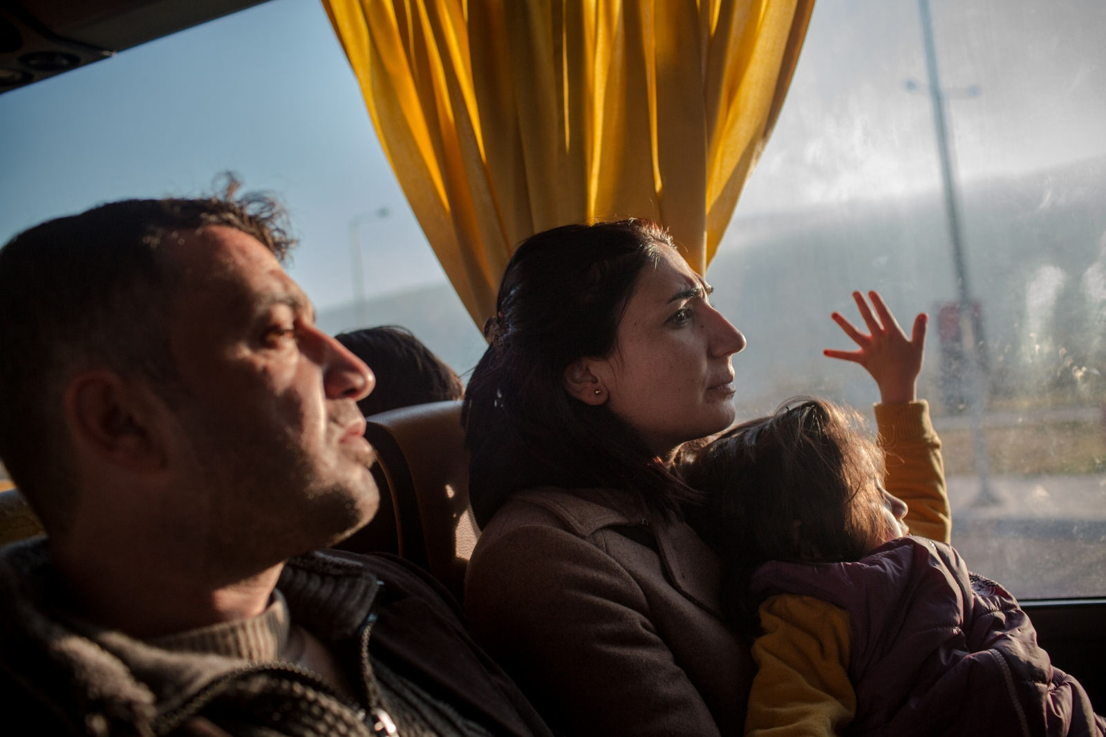 Tariq, left, Nisreen, and their five-year old daughter Roslyn, are seen on the day-long bus ride from Athens to the Greek-Macedonian border in the far north, as they continue their journey from Syria to Germany, on December 19, 2015.